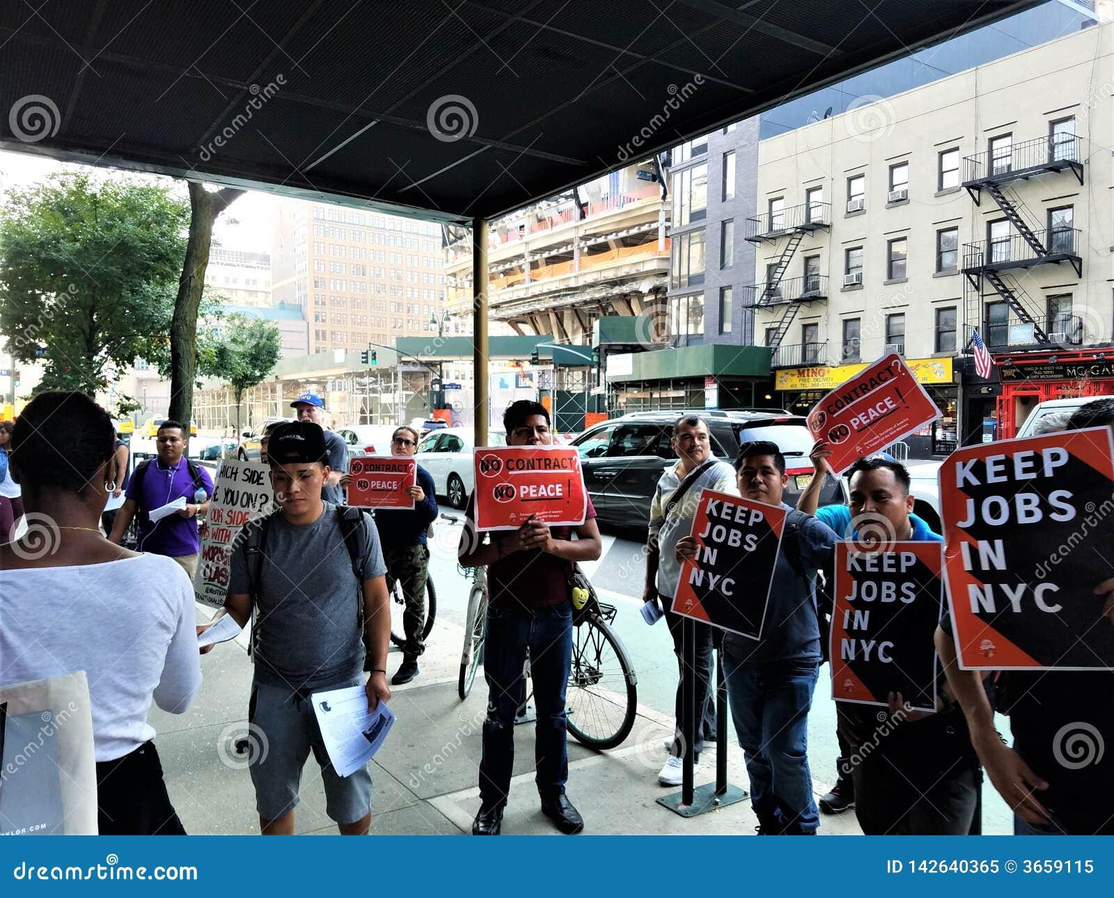 La gente fuera de la tienda de la foto de B&H en Manhattan con las muestras mantiene trabajos NYC en las manos que protesta con l
