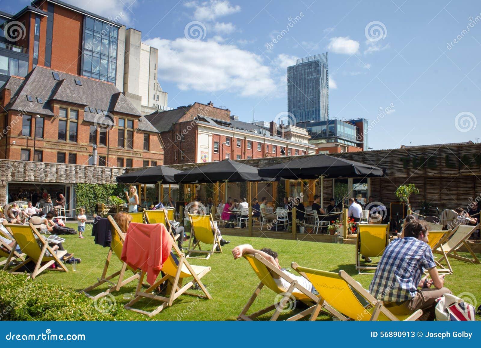 La gente gode del sole nel centro urbano Spinningfields, Manchester Regno Unito