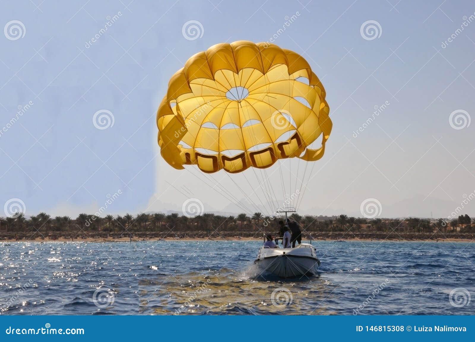 La gente guida una barca con un paracadute