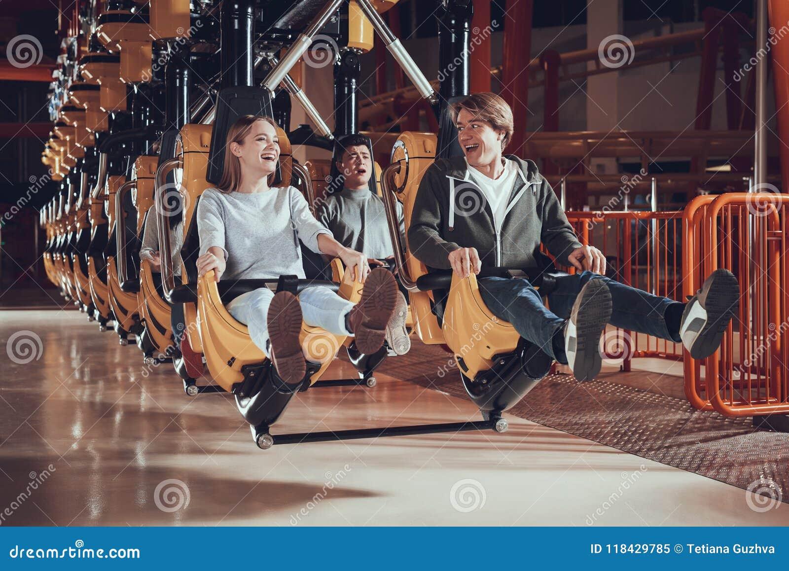 La gente joven aumenta sus pies mientras que se sienta en el carrusel