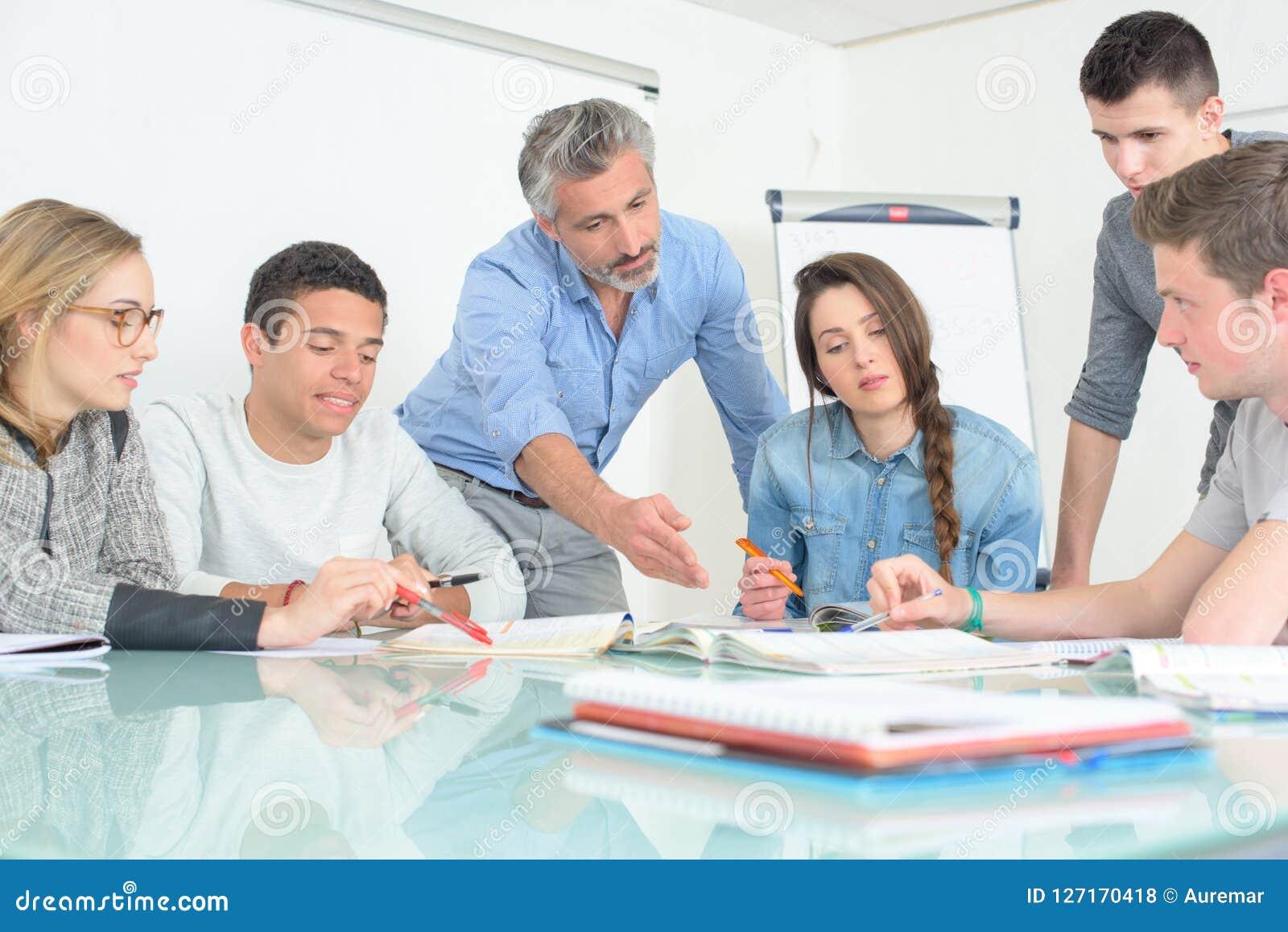 La gente joven que el profesor discute comunica la sala de clase de la universidad