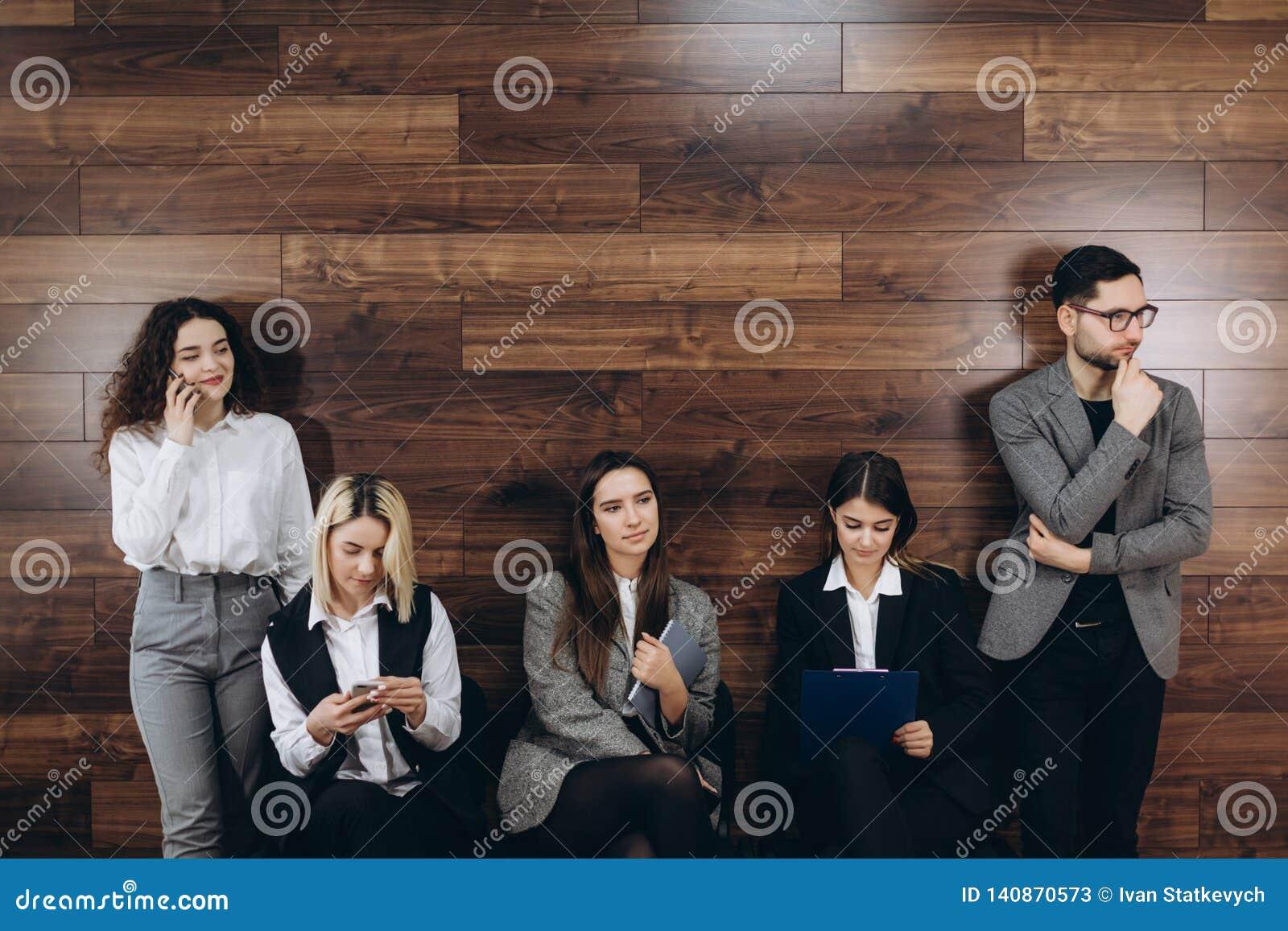 La gente milenaria Multi-étnica que sostiene los teléfonos y los curriculums vitae que se preparan para la entrevista de trabajo,