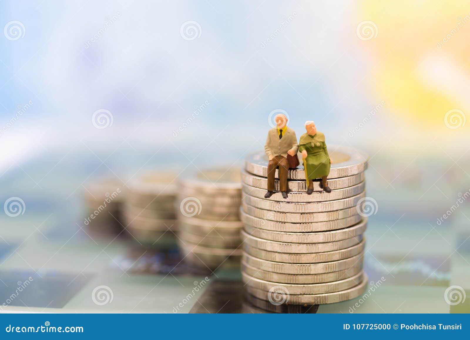 La gente miniatura, los viejos pares figura la situación encima de monedas de la pila Uso de la imagen para la planificación de l