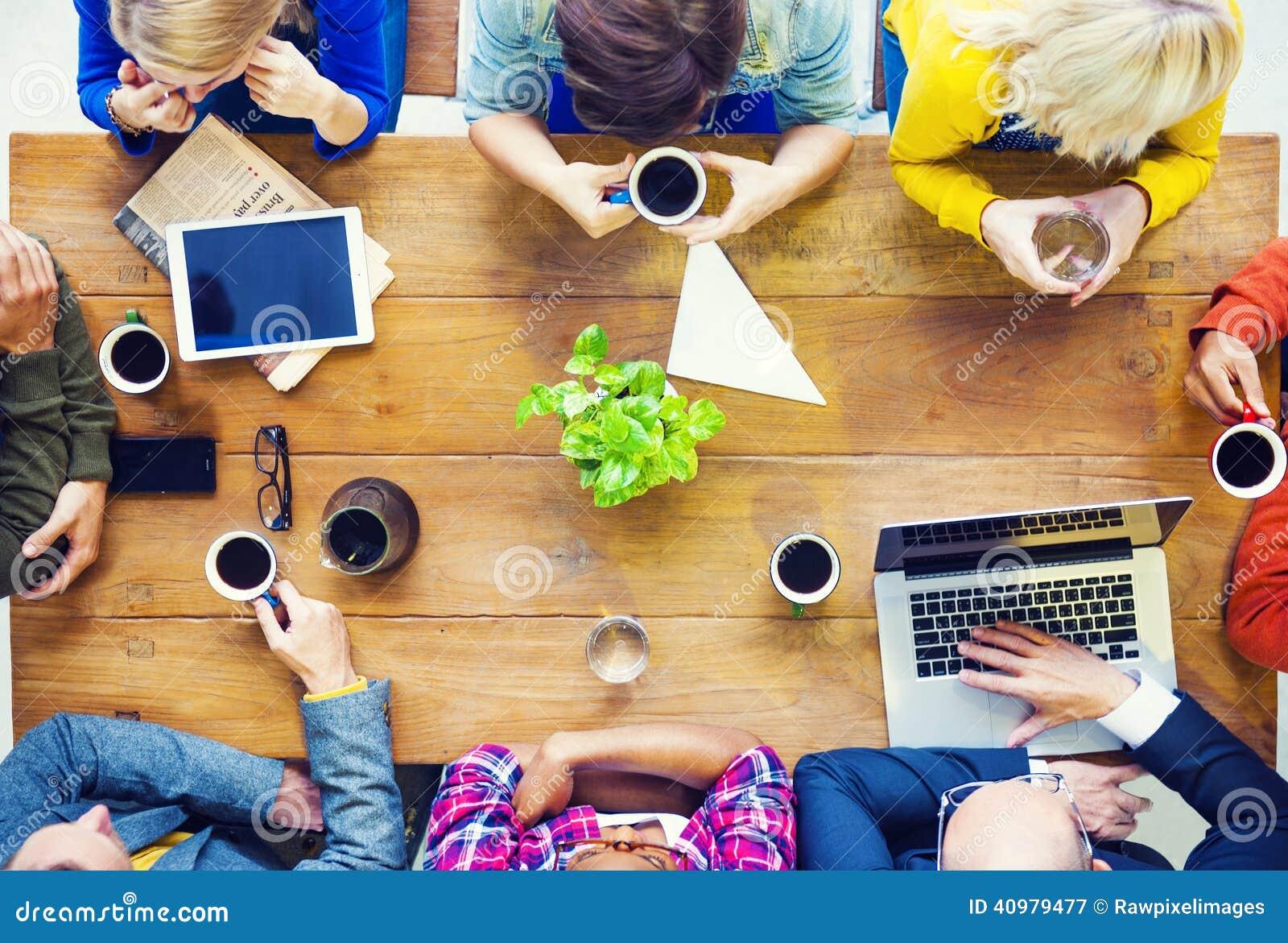 La gente multietnica con inizia sull attività che parla in un caffè