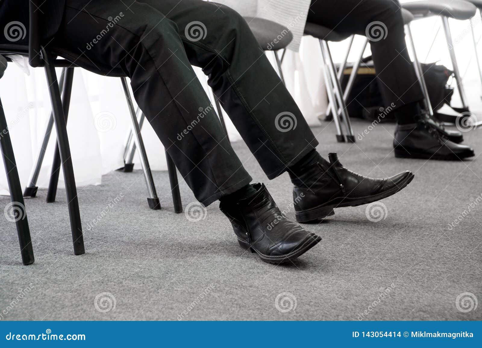 La gente parada espera su vuelta una entrevista, sentándose en sillas de la oficina en el vestíbulo Búsqueda del desempleo y de t