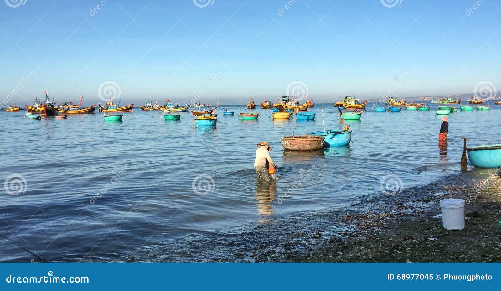 La gente que trabajaba en la playa con muchos barcos de pesca en Phan sonó, Vietnam