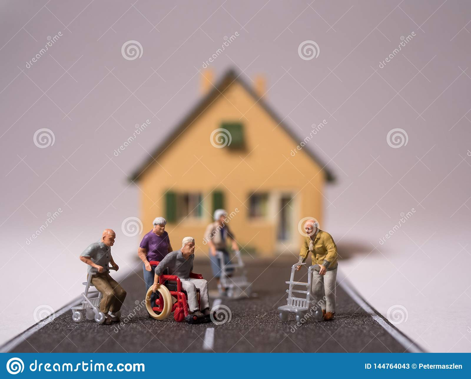 La gente senior di Minitature con la sedia a rotelle ed i camminatori ha lasciato solo sulla via
