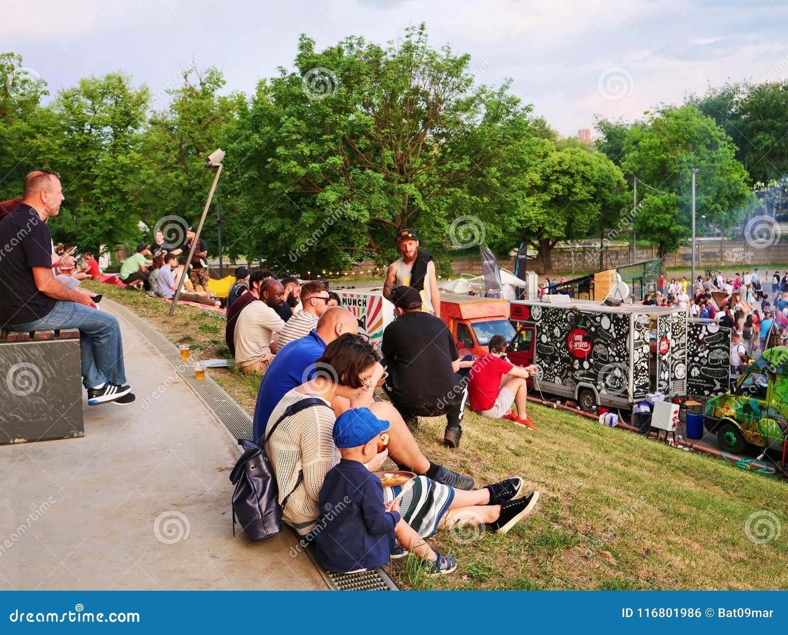 La gente si siede sull erba ed ha uno spuntino