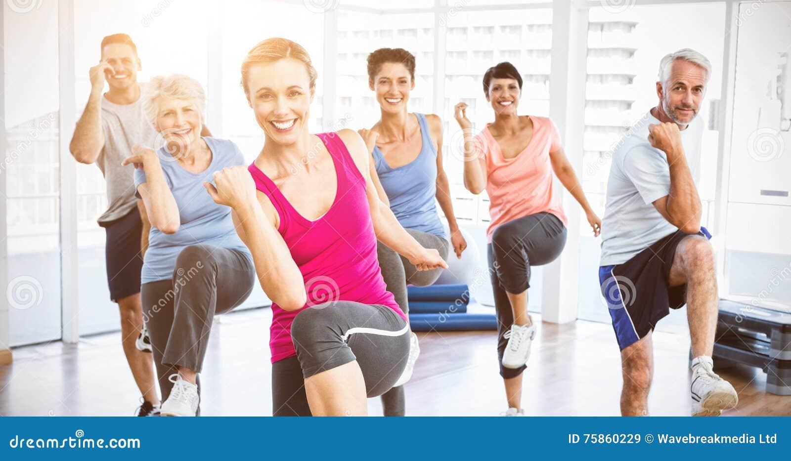 La gente sonriente que hace aptitud del poder ejercita en la clase de la yoga