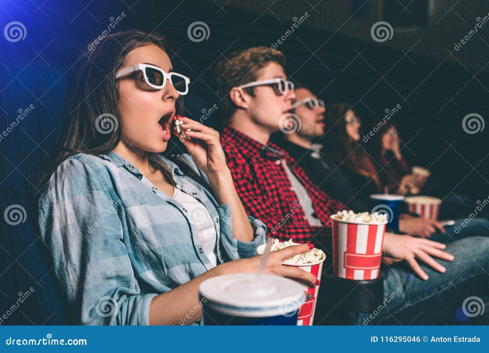 La gente sorprendente y sorprendida se está sentando en una fila y película de observación La muchacha rubia está comiendo las pa