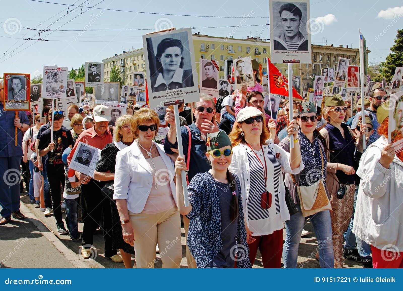 La gente sostiene los retratos de sus parientes en el ` inmortal del regimiento del ` de la acción el día de la victoria en Stali