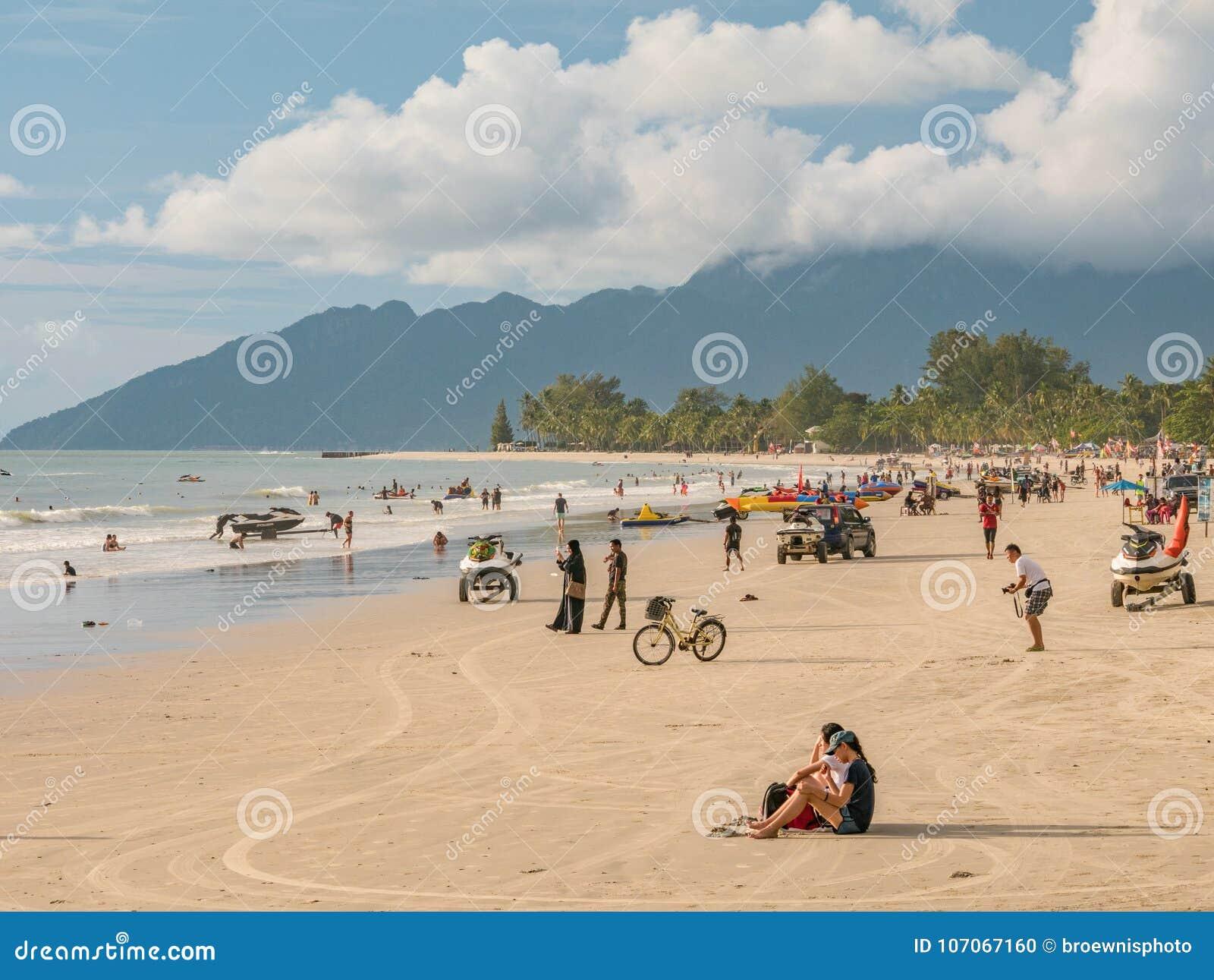 La gente sul tramonto aspettante della spiaggia alla - Alla colorazione della spiaggia ...