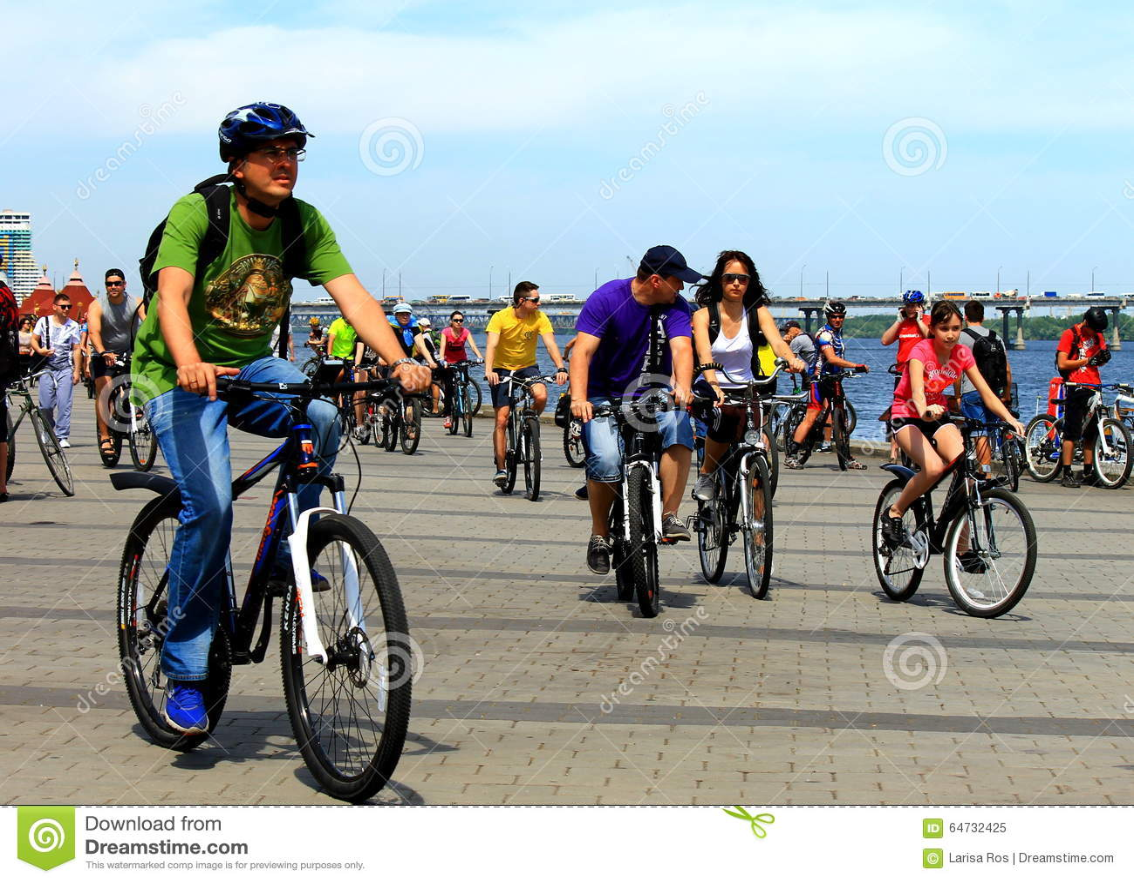 La gente sulle biciclette che guidano sulla via della città