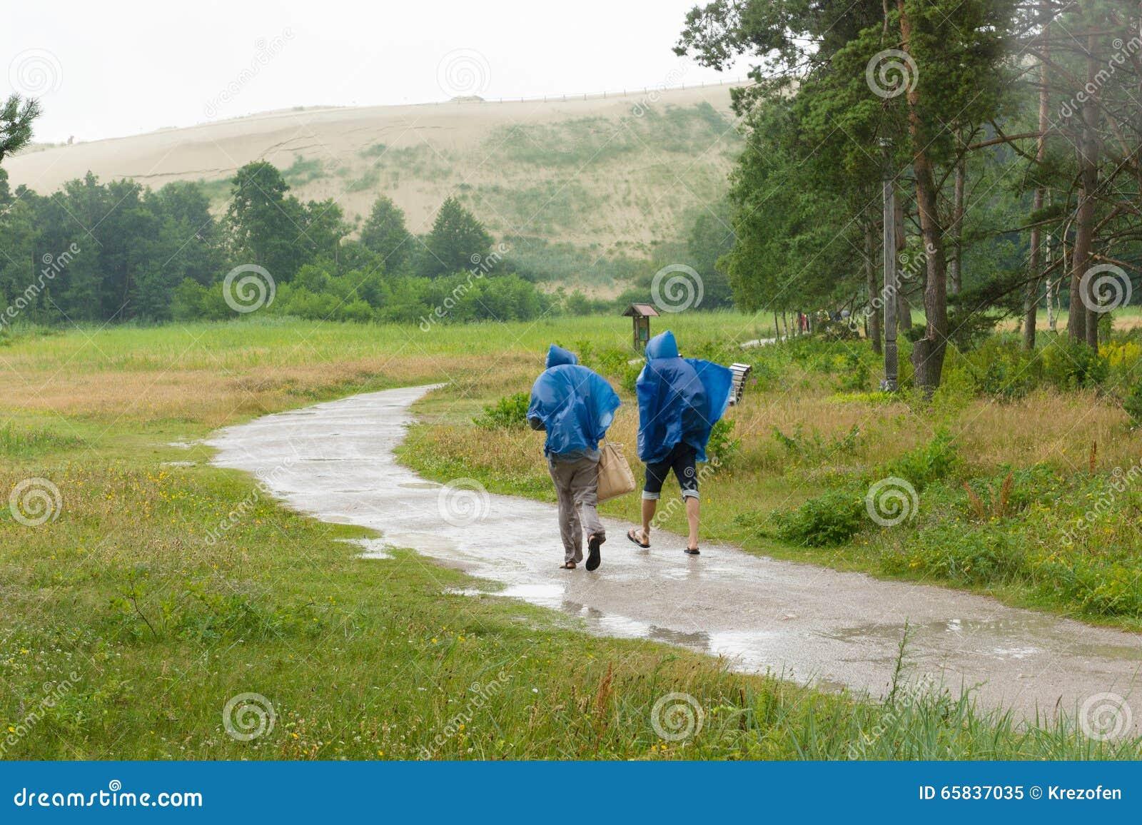 La gente va en el camino en la lluvia