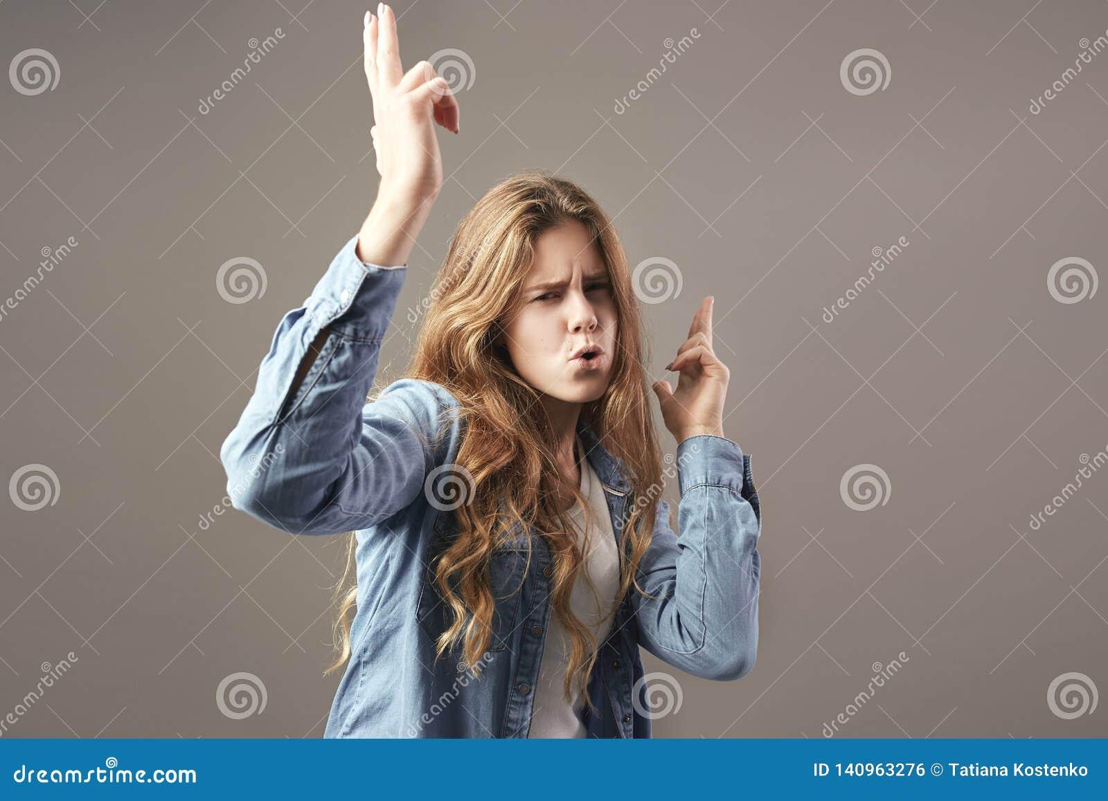 La gentille fille avec de longs cheveux bruns habillés dans un T-shirt blanc, les jeans et la chemise de jeans dupe autour sur un