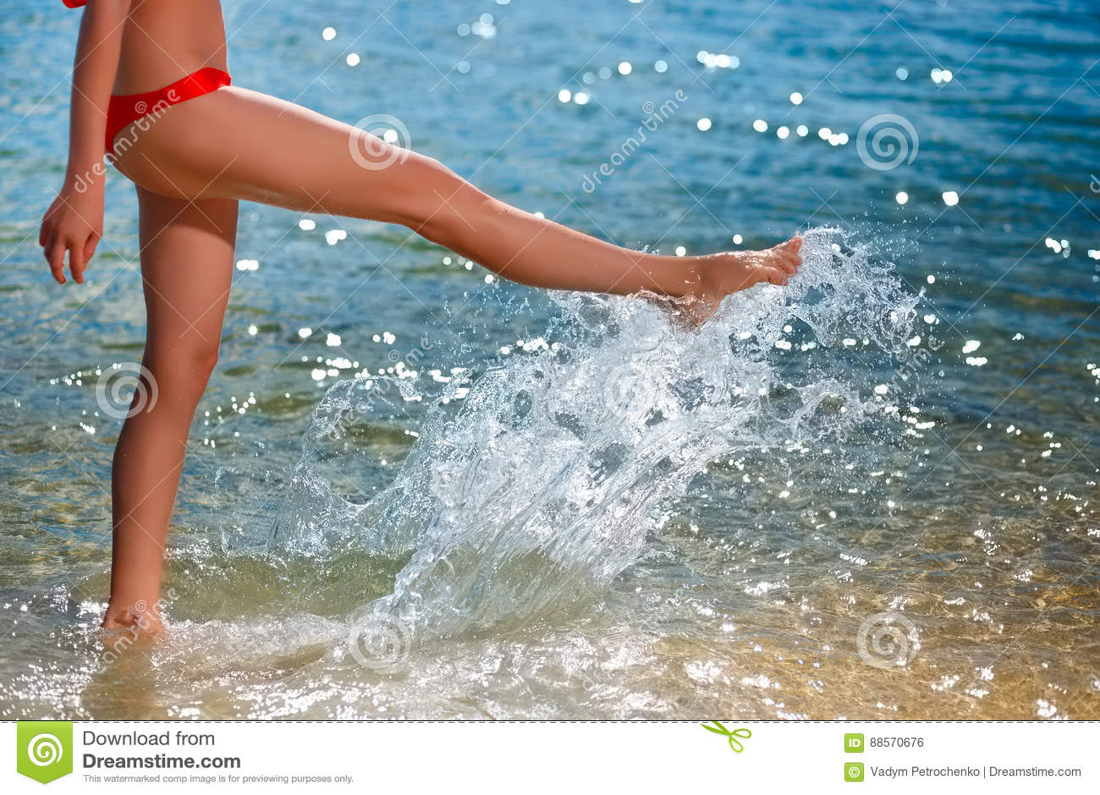 La giovane bella donna che cammina sulla spiaggia e spruzza l acqua vicino