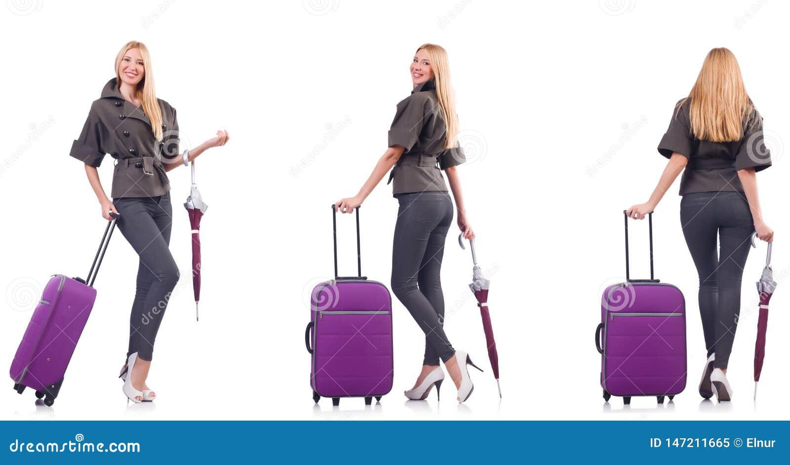La giovane bella donna con la valigia e l ombrello isolati su bianco