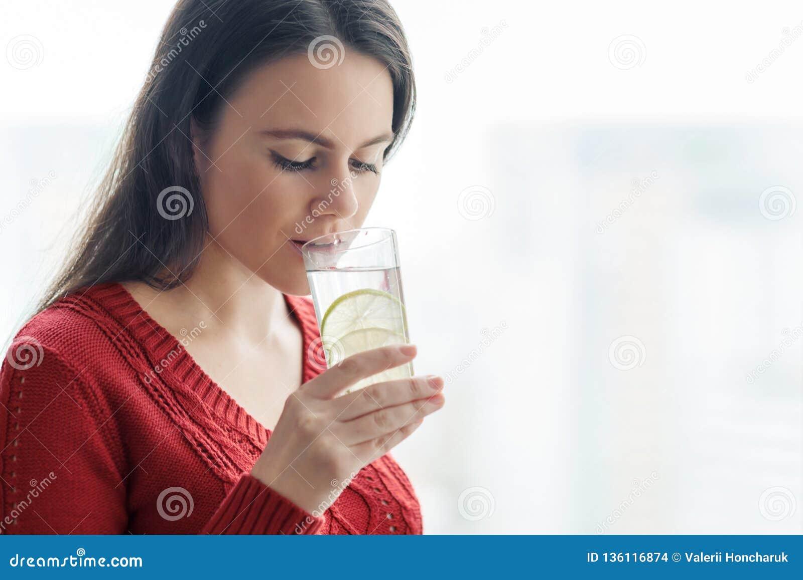 La giovane bella donna in maglione rosso con bicchiere d acqua con calce, donna sta vicino alla finestra in grattacielo il giorno