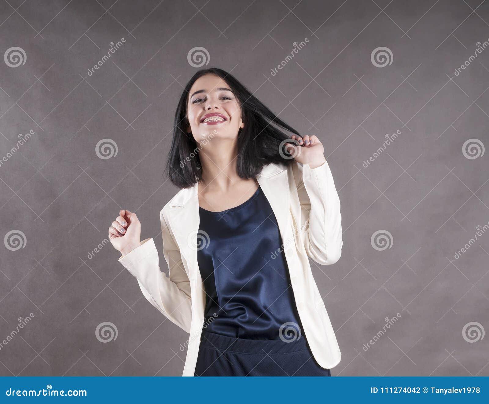 La giovane bella espressione felice della donna di affari rinforza lo studio castana