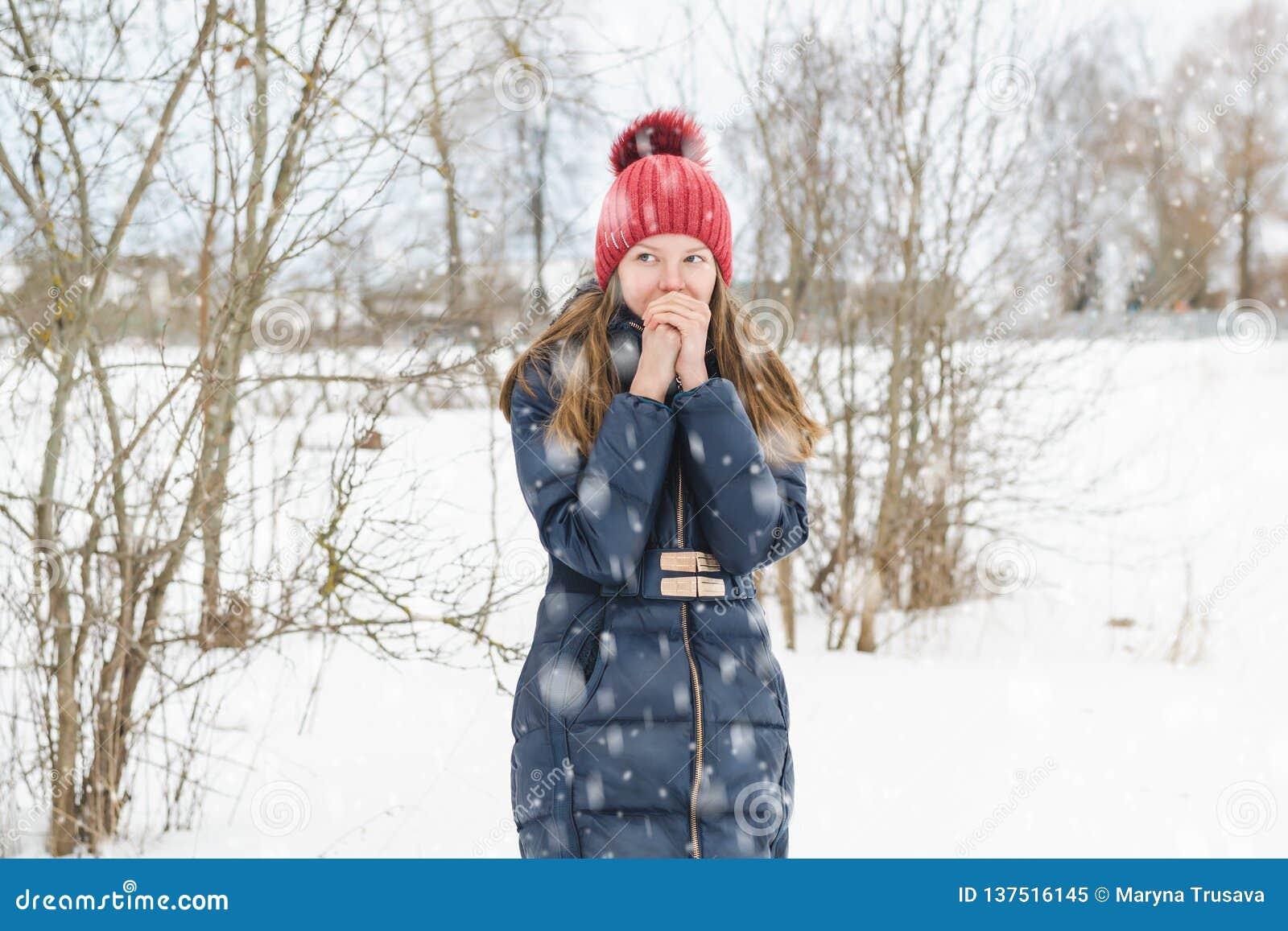 La giovane bella ragazza bionda respira sulle sue mani per riscaldarle nel parco sotto neve lanuginosa molle