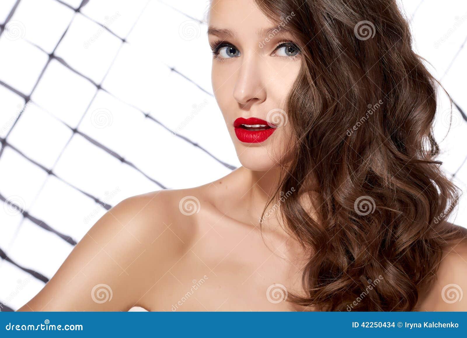 La giovane bella ragazza sexy con capelli ricci scuri con la spalla nuda  rossa di trucco luminoso degli occhi azzurri e delle labbra esamina allegro  la ... 4b3773ac930b