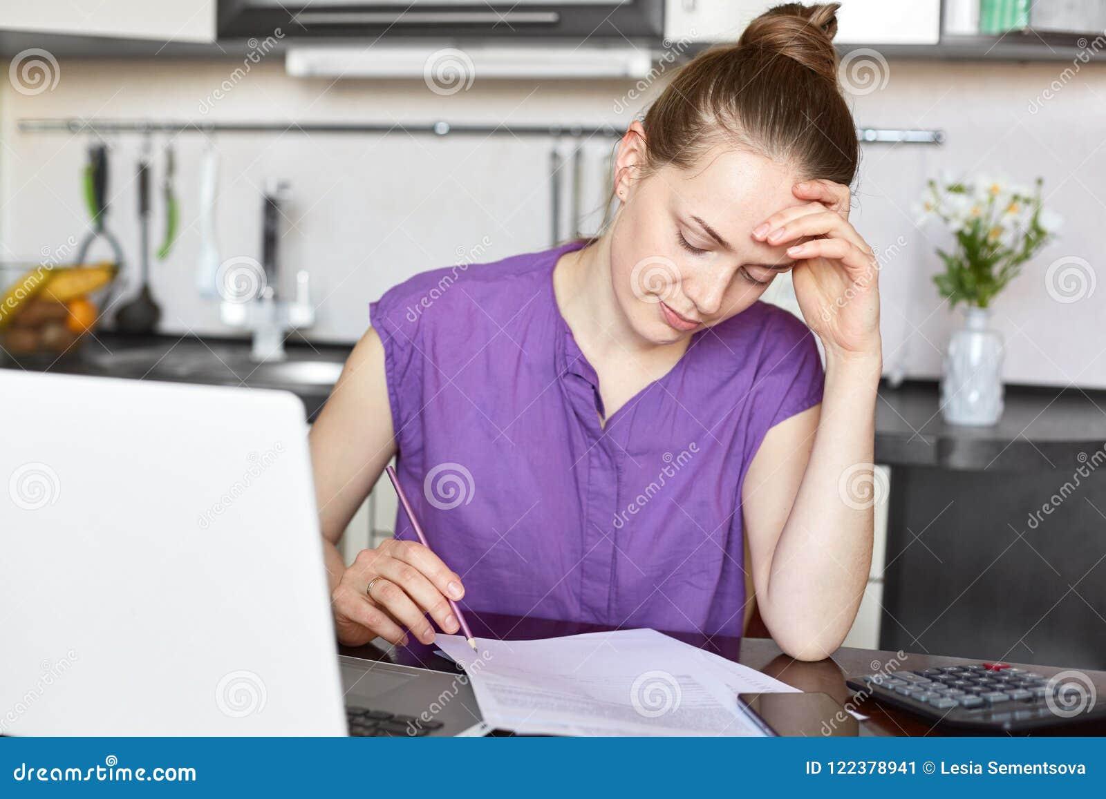 La giovane casalinga calcola le spese di famiglia, deve fogli paga per affitto ed il gas, esamina le carte, funziona con il compu