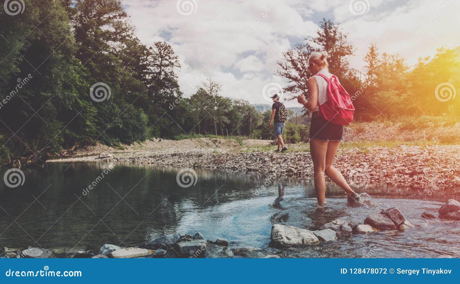 La giovane coppia sta camminando lungo la banca di un fiume della montagna di estate Una ragazza con un gatto selvatico attravers