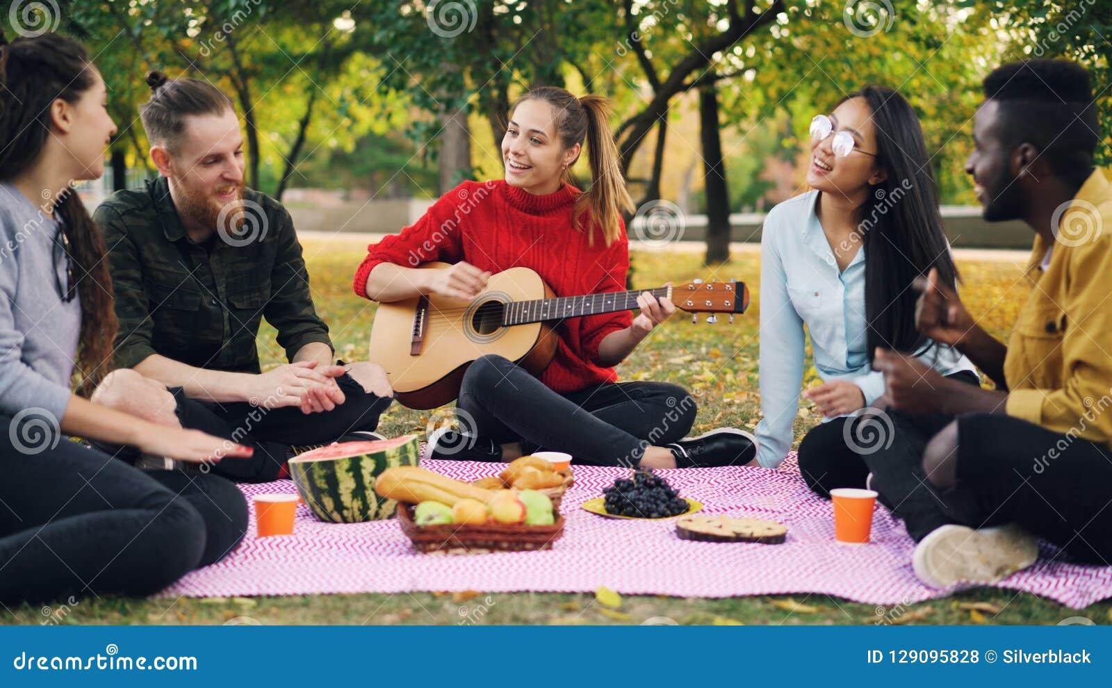 La giovane donna affascinante sta giocando la chitarra che si siede sulla coperta con gli amici sul picnic, ragazze ed i tipi sta