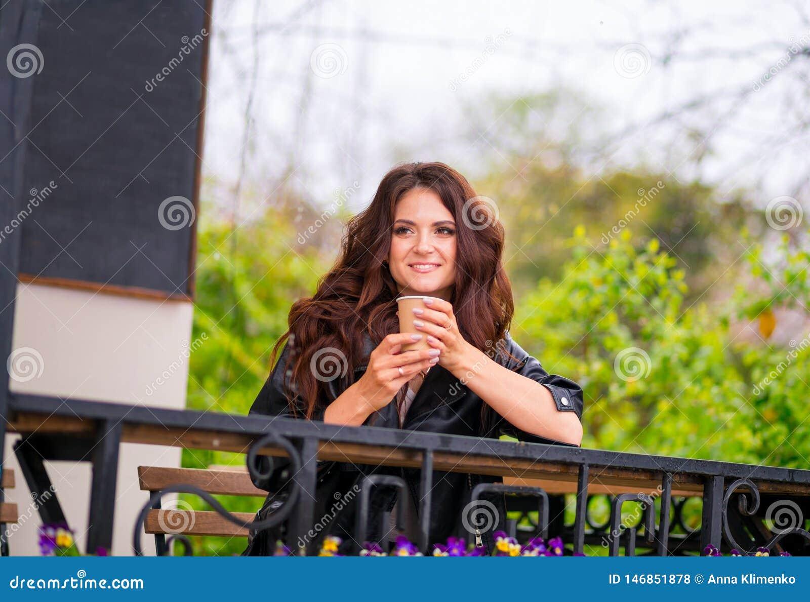 La giovane donna allegra graziosa in rivestimento del lether si siede sul caff? bevente del terrazzo del caff? dalla tazza di car