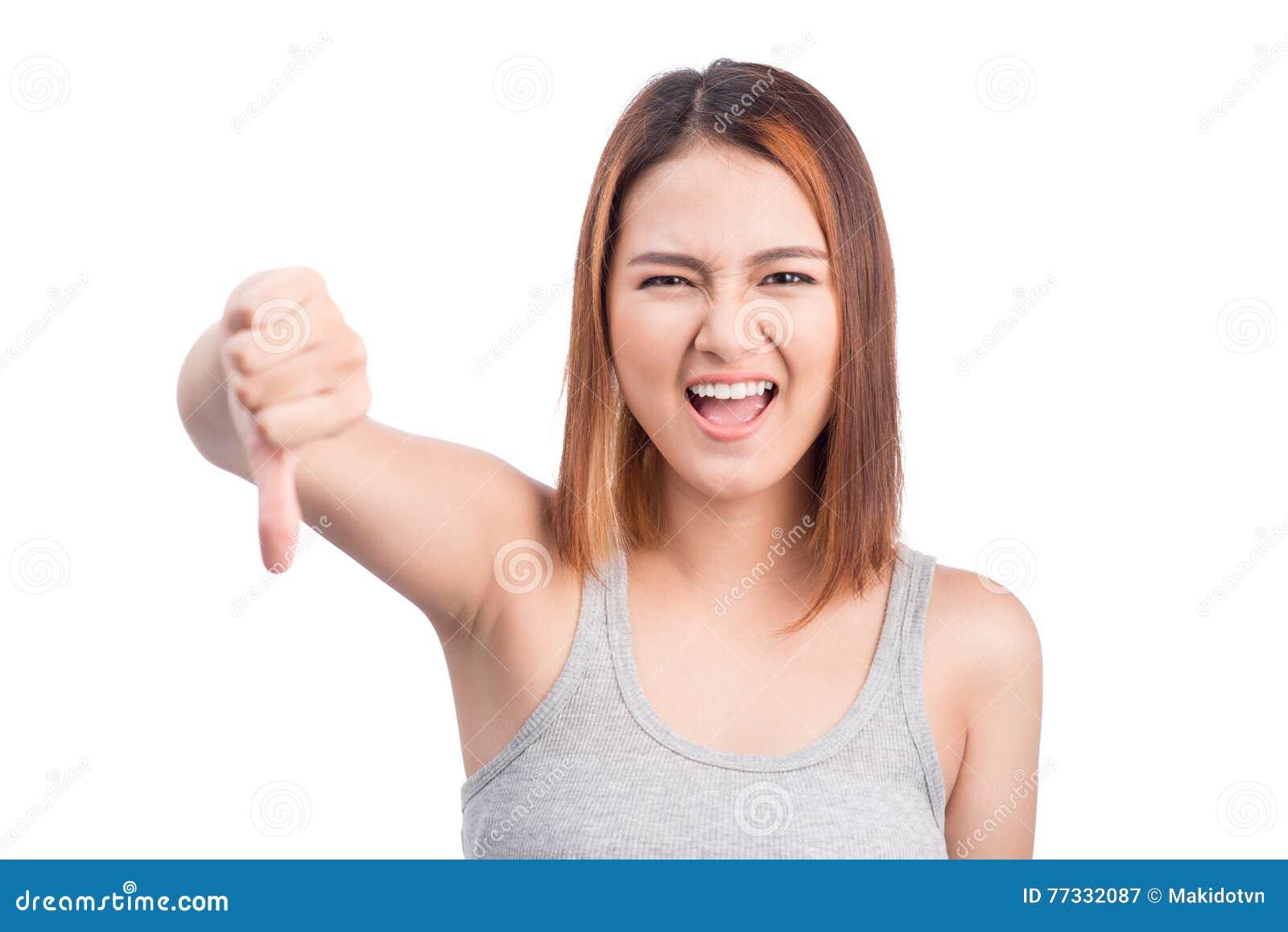 La giovane donna asiatica infelice che dà i pollici giù gesture guardando lo spirito
