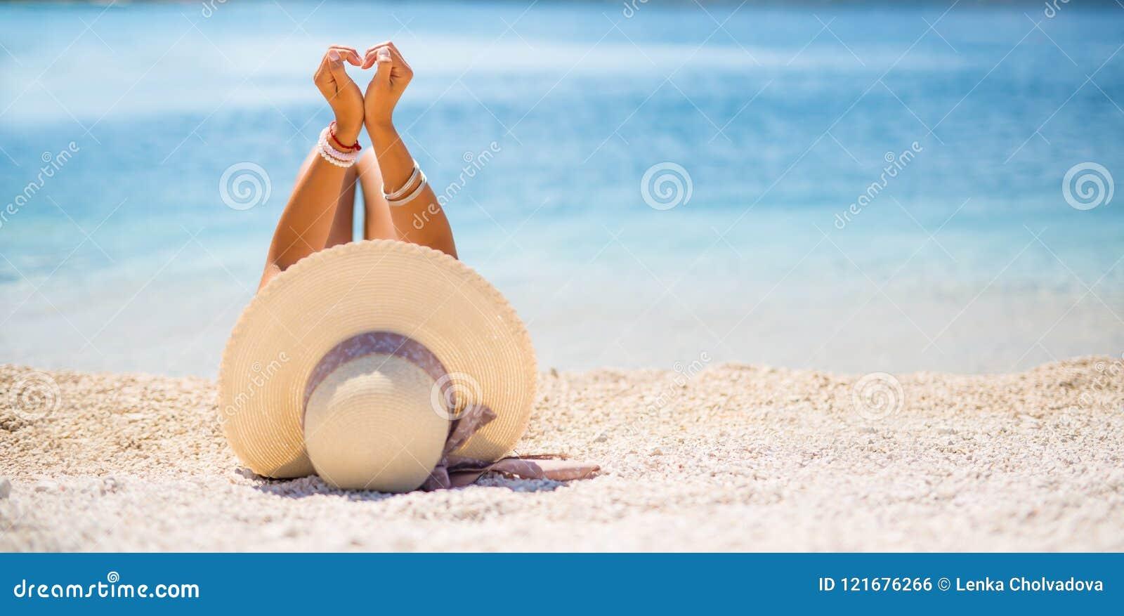 La giovane donna attraente con il cappello si trova sulla spiaggia