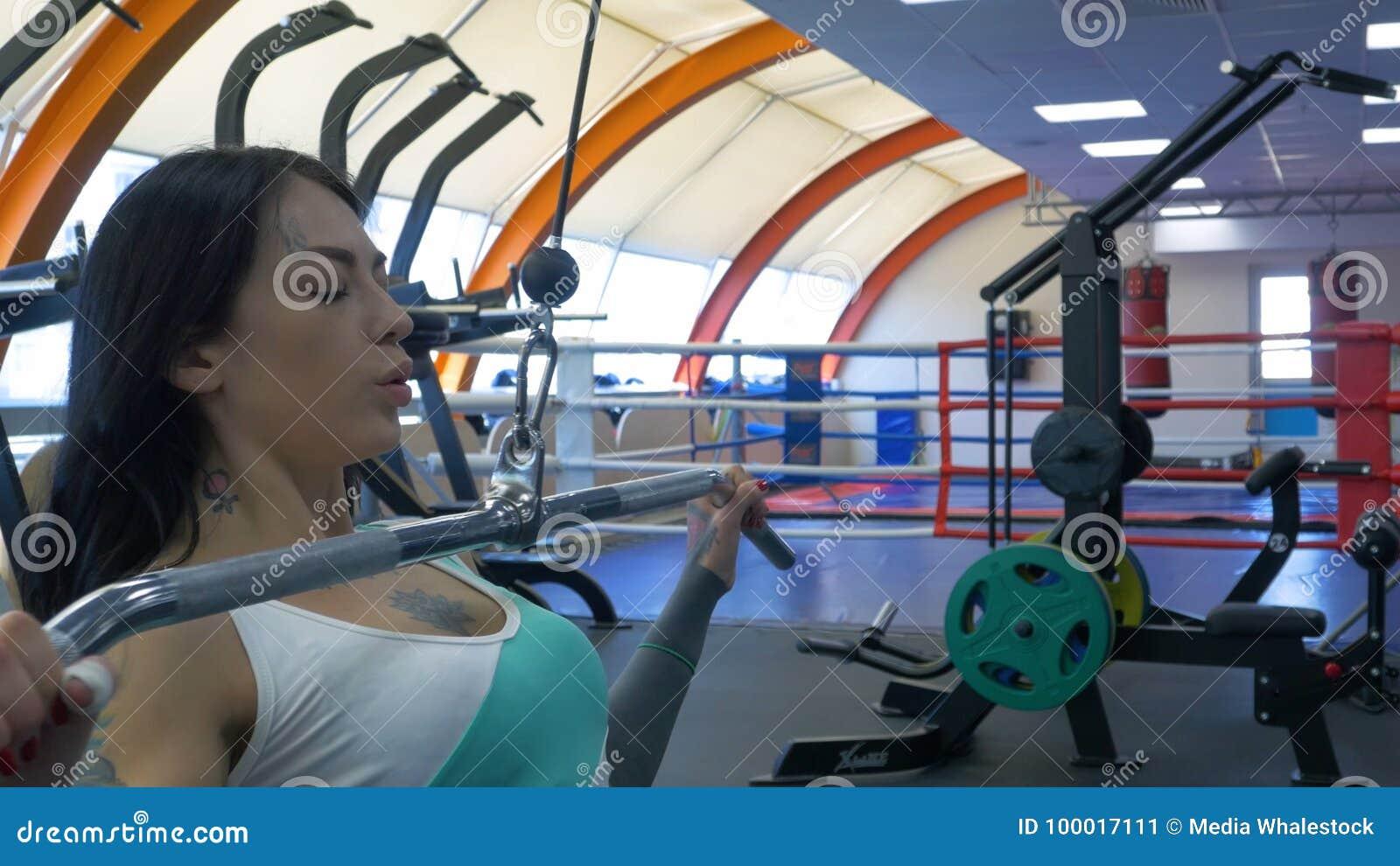 La giovane donna attraente sta risolvendo su una stazione di forma fisica in palestra, pompante il ferro Addestramento uscente de