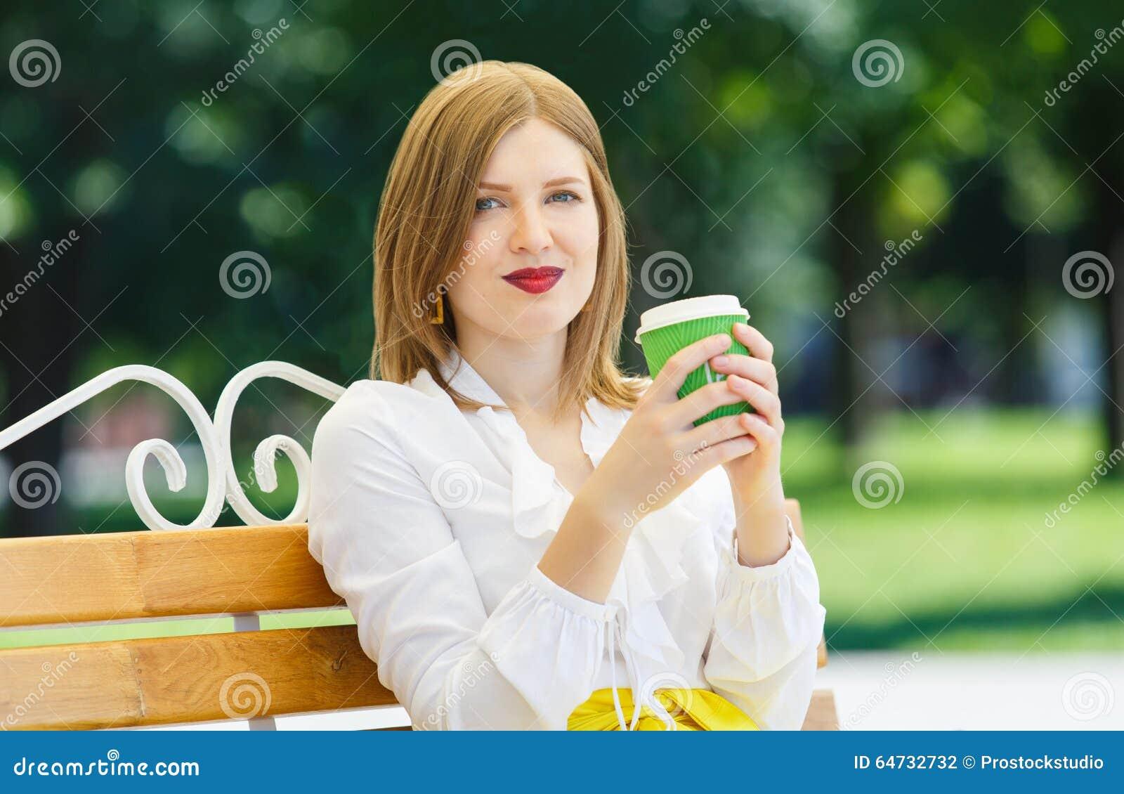 La giovane donna beve il caffè nel parco