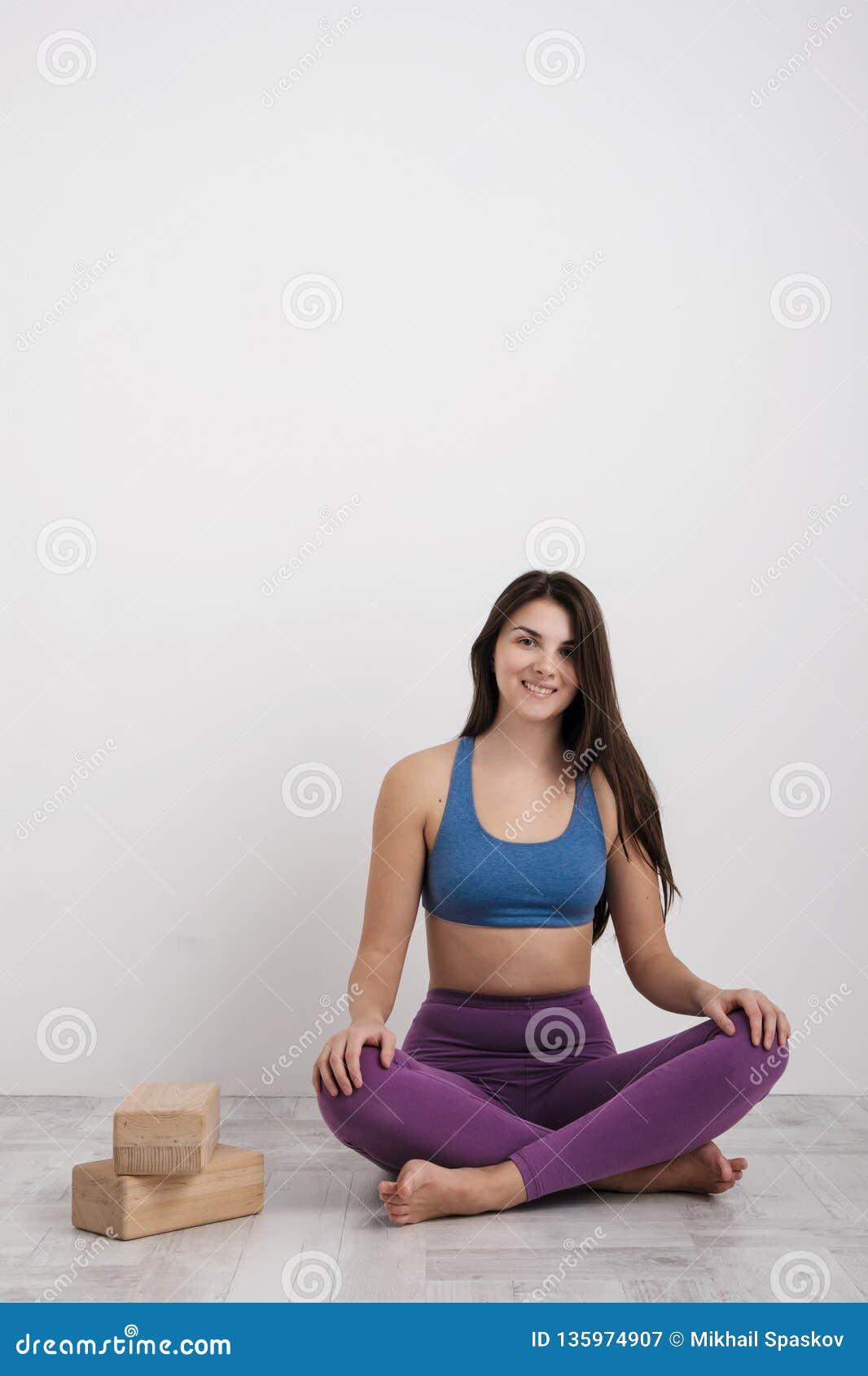 La giovane donna castana in ghette porpora ed in una maglietta di sport fa gli esercizi sul pavimento Equilibri sui blocchi e