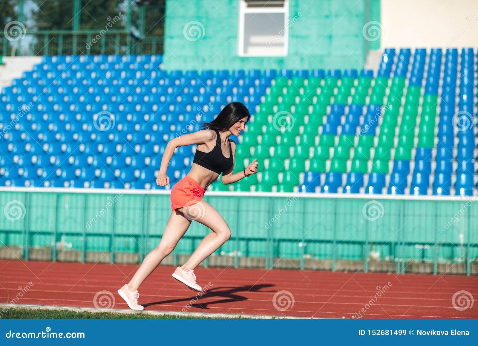 La giovane donna castana sportiva in rosa mette e canottiera sportiva che corre allo stadio Stile di vita attivo sano Attivit? di