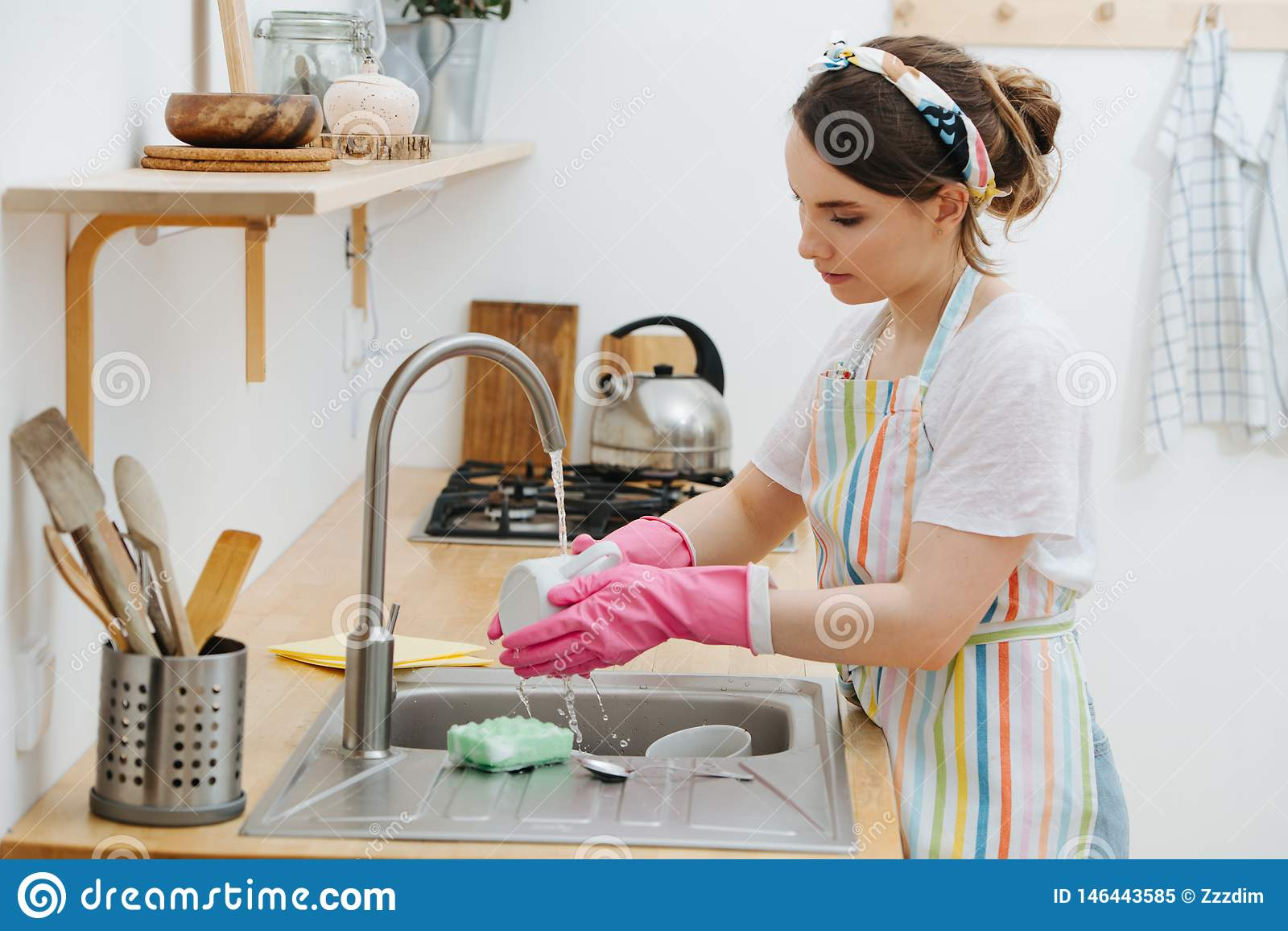 La giovane donna castana in una cucina sta lavando le tazze ed i piatti