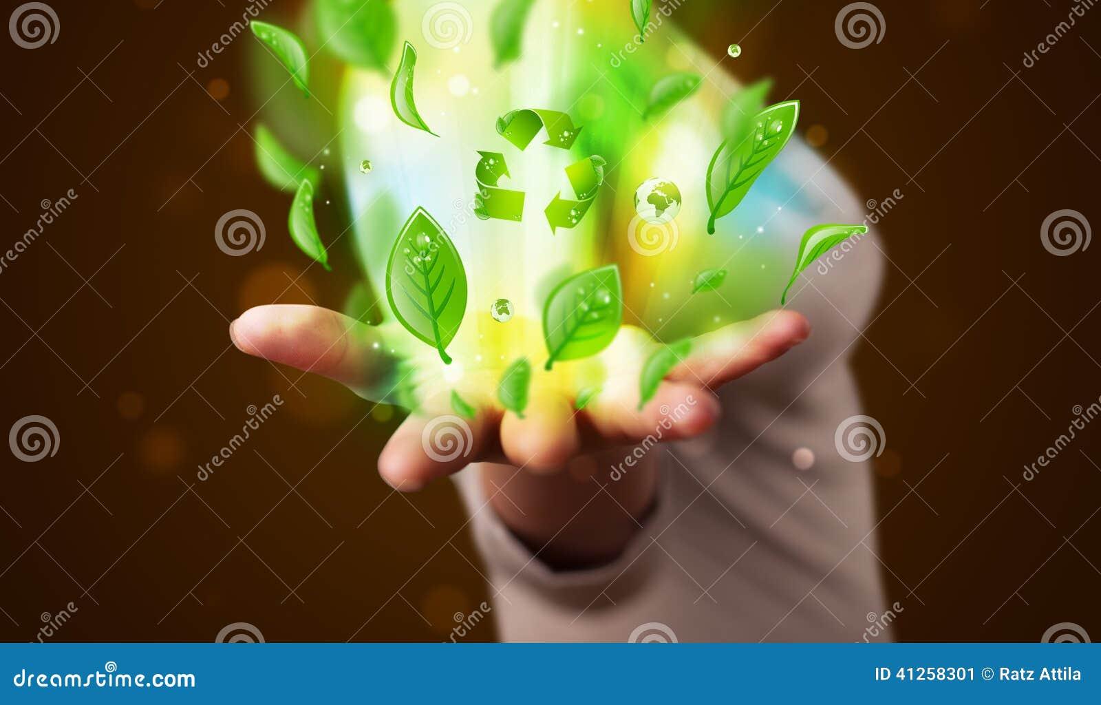 La giovane donna che presenta a eco la foglia verde ricicla il concetto di energia