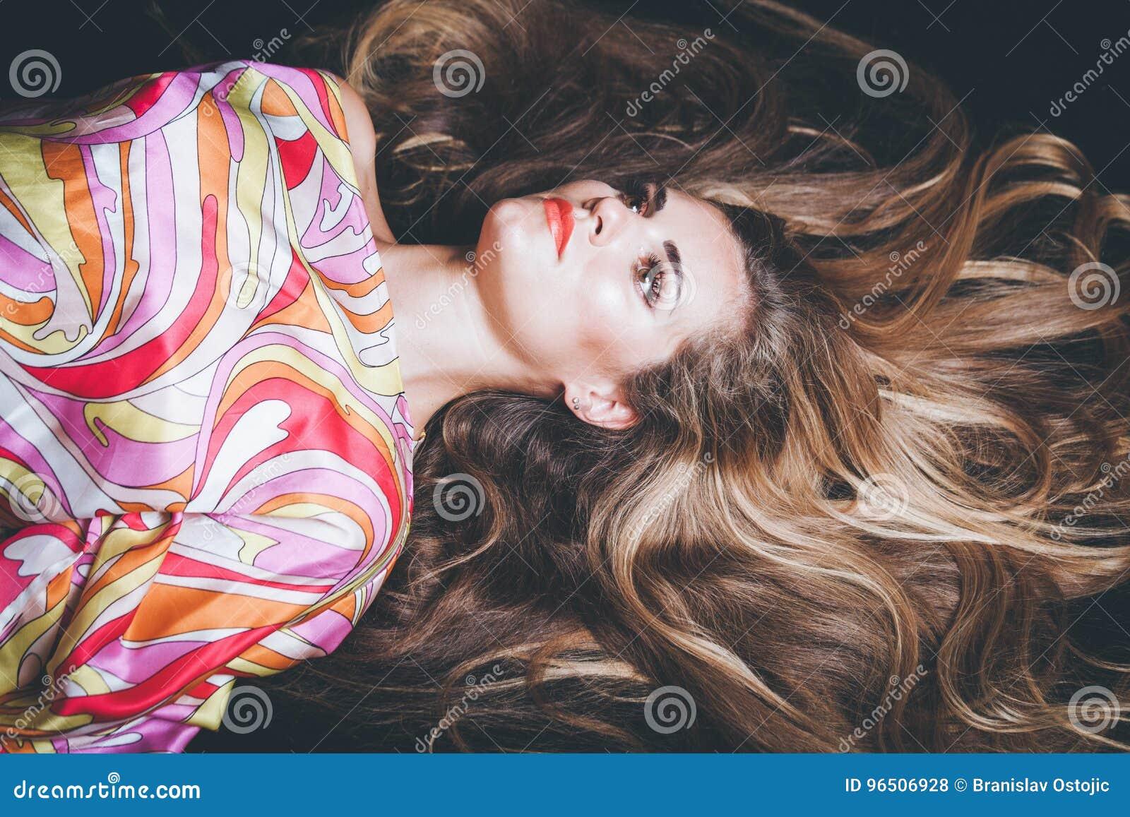 La giovane donna con capelli biondi molto lunghi si riposa il colpo dello studio