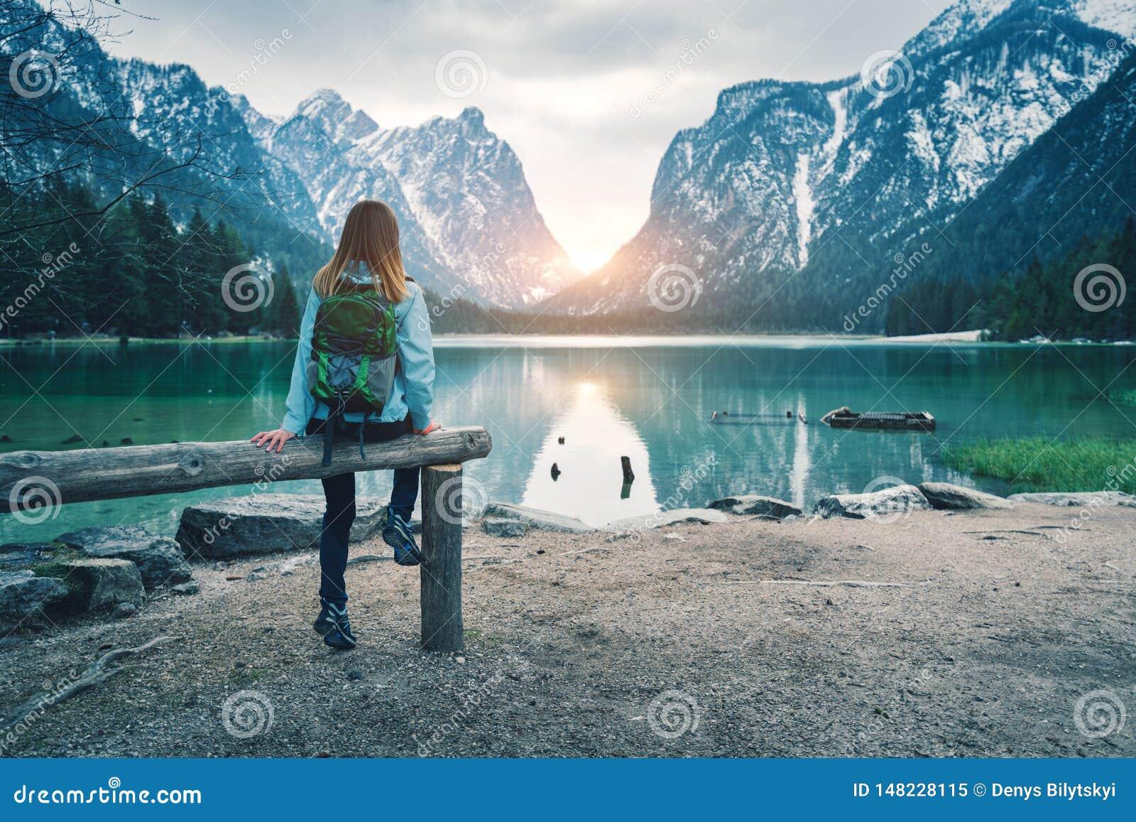 La giovane donna con lo zaino sta sedendosi sulla costa del lago