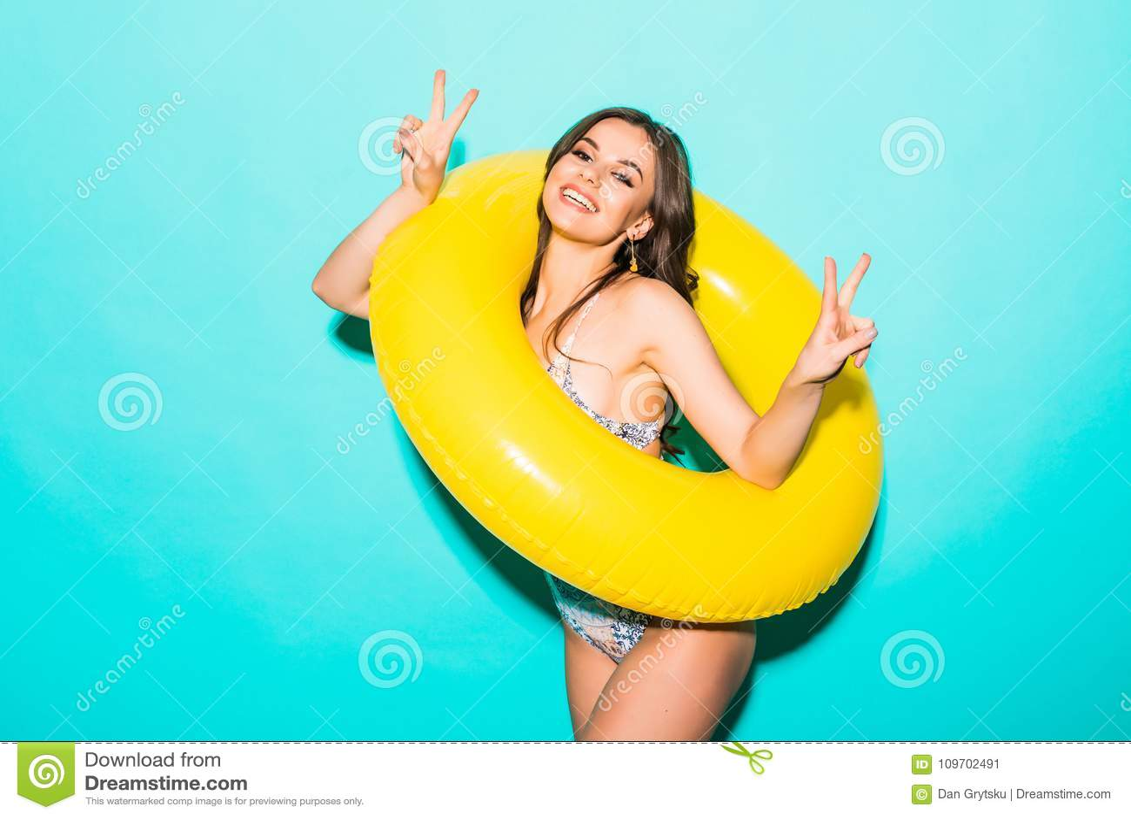 La giovane donna in costume da bagno con un anello gonfiabile e la mano che mostra la vittoria gesture sopra fondo blu
