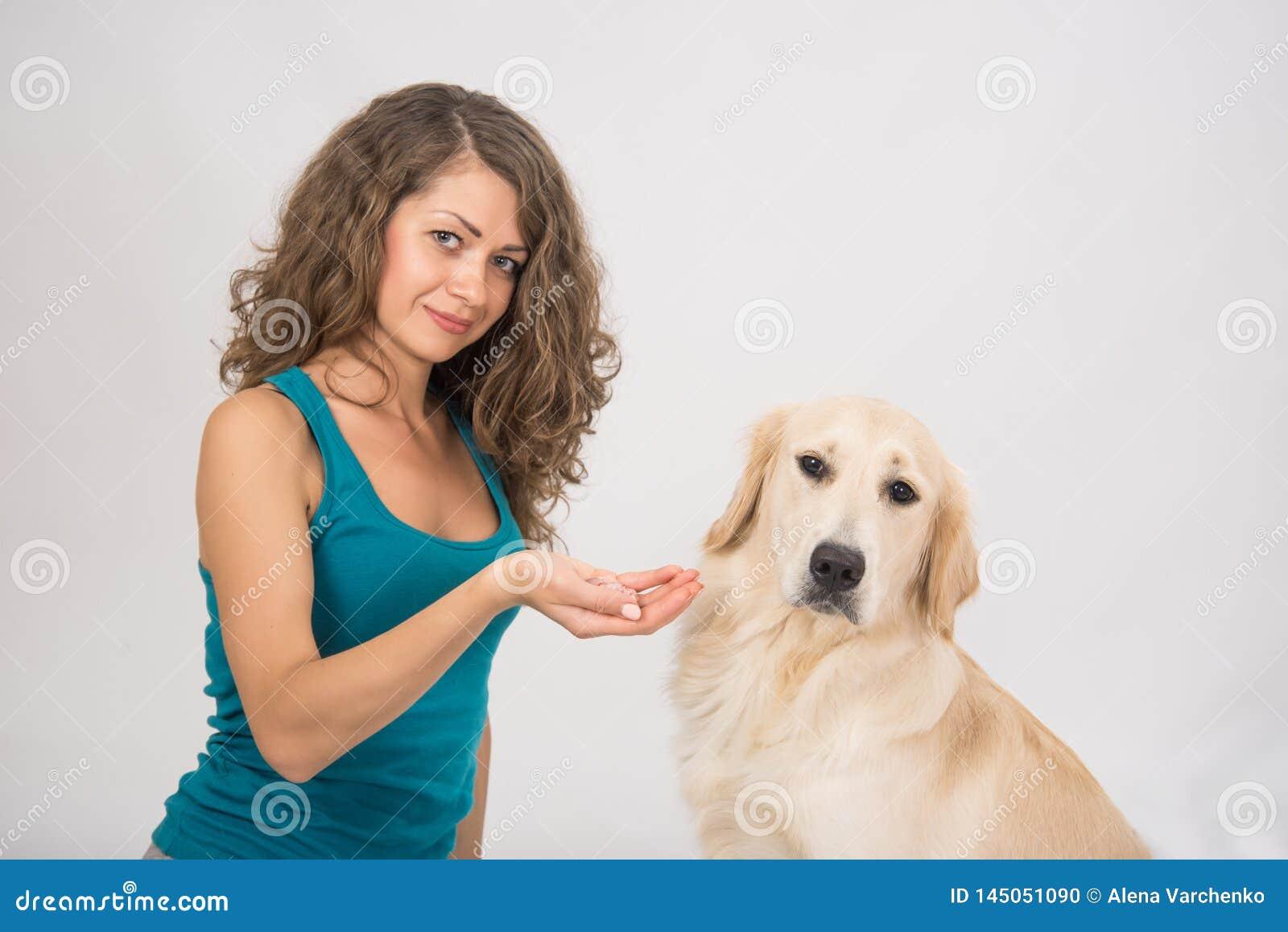 La giovane donna dà un pezzo di carne al suo cane