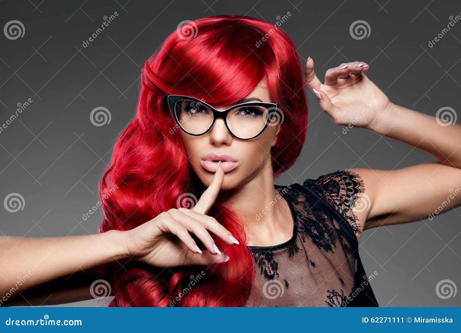 La giovane donna d avanguardia di modo di lusso con rosso ha arricciato i capelli in glas