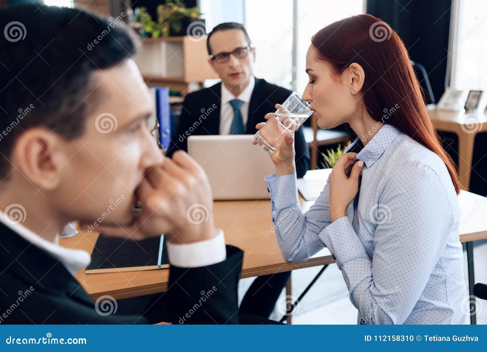 La giovane donna dai capelli rossi è bicchiere dell acqua, sedentesi accanto all uomo adulto nell ufficio del ` s dell avvocato d