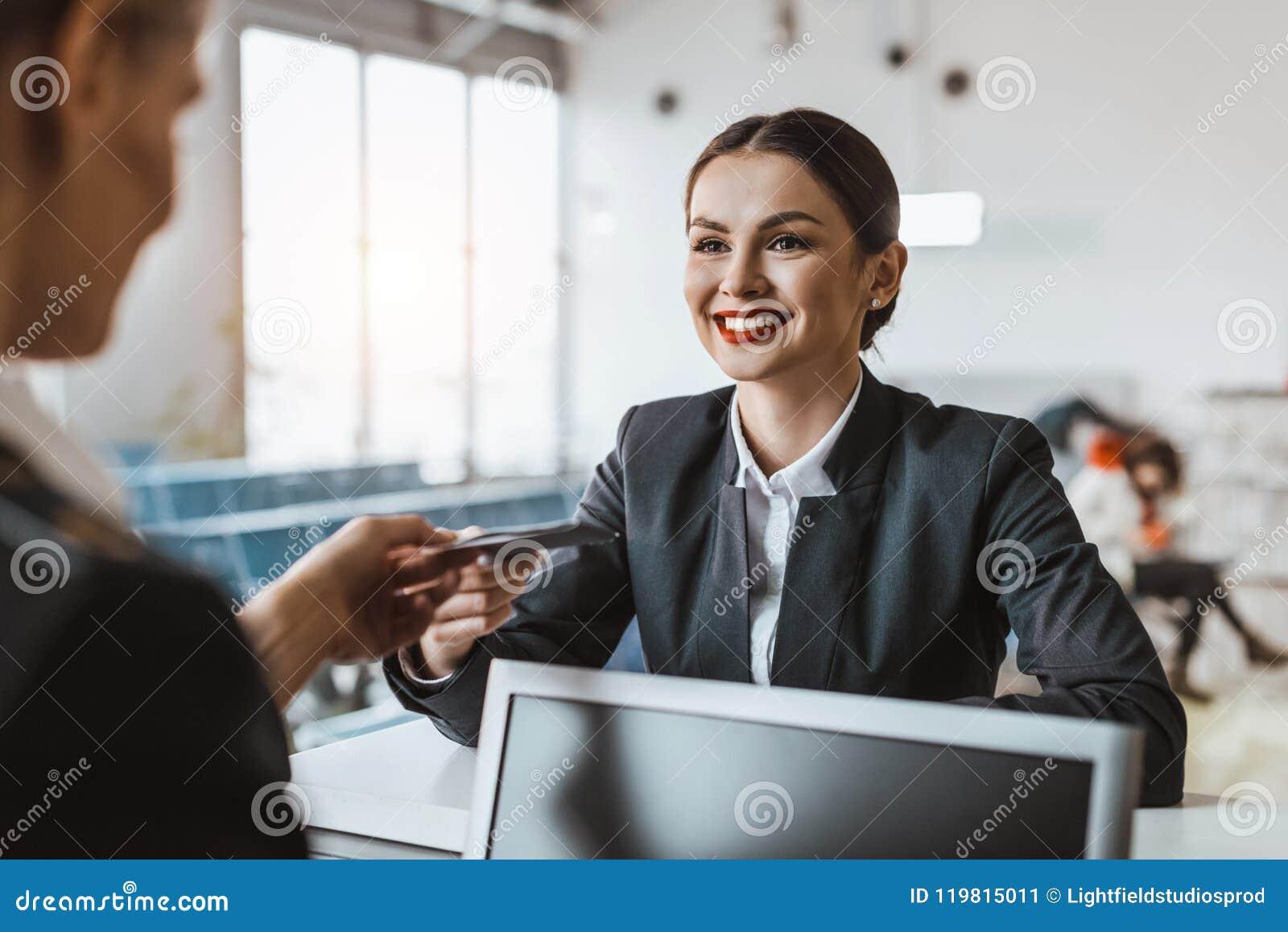 La giovane donna di affari attraente che danno il passaporto ed il biglietto al personale all aeroporto controllano