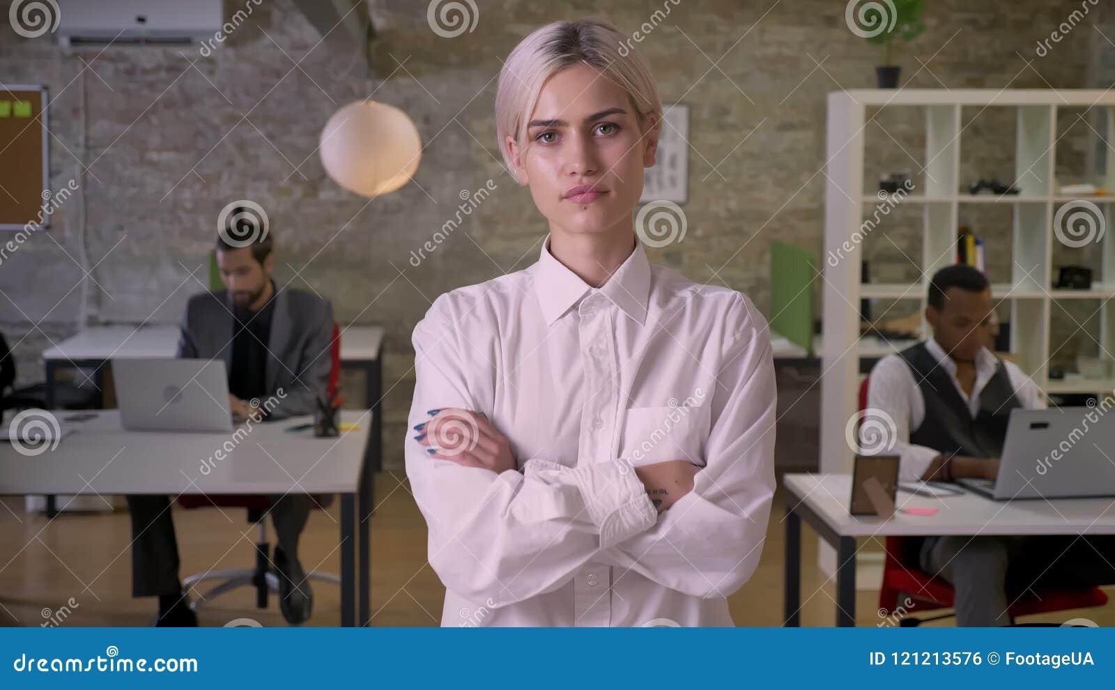 La giovane donna di affari graziosa è stante ed attraversando le sue armi in ufficio, i colleghi stanno lavorando con i computer  archivi video