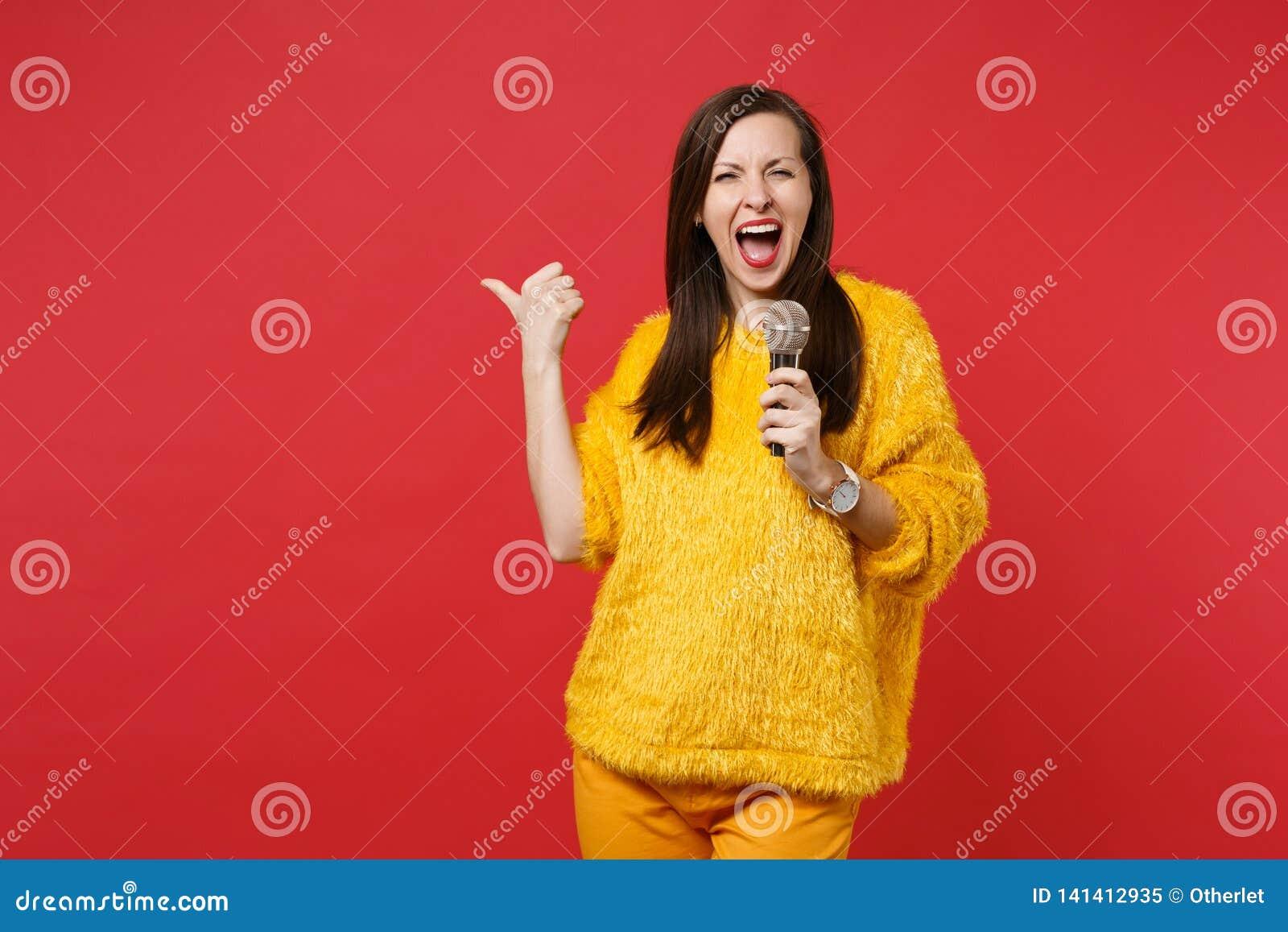 La giovane donna divertente in maglione giallo della pelliccia che indica il pollice da parte, canta la canzone in microfono isol