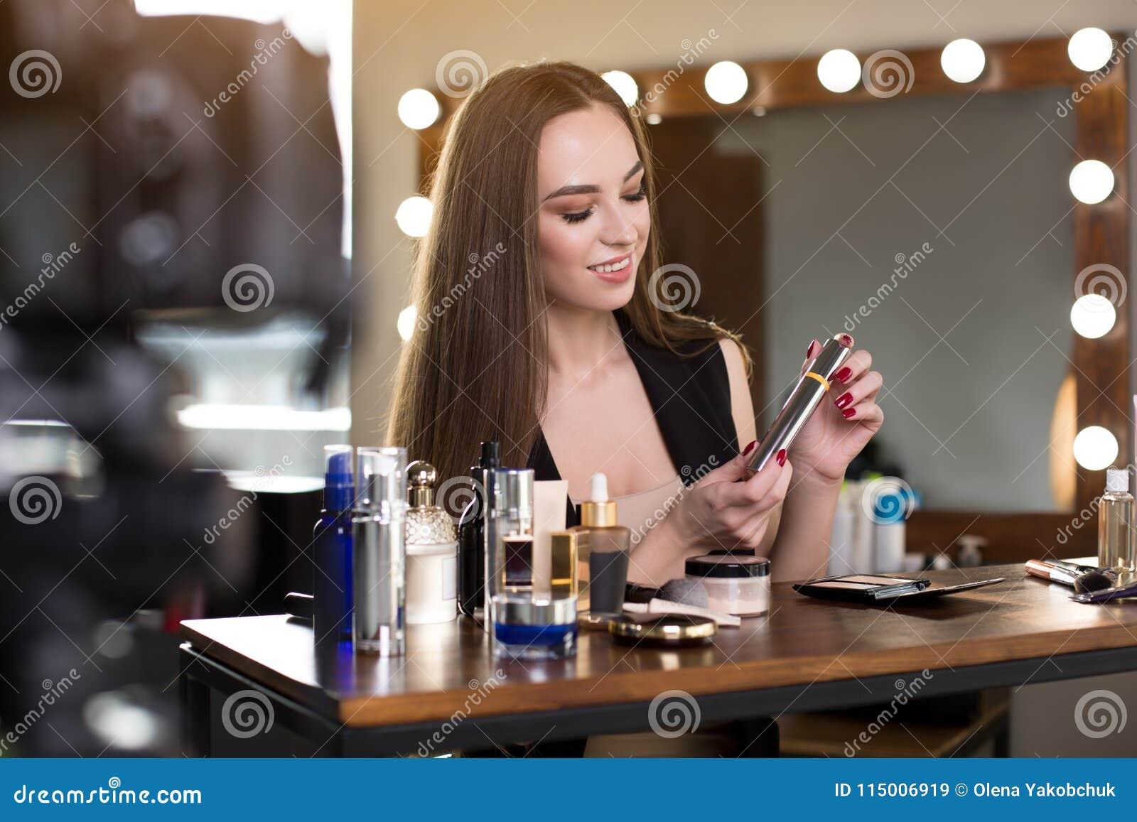 La giovane donna elegante piacevole sta registrando il video per il suo blog