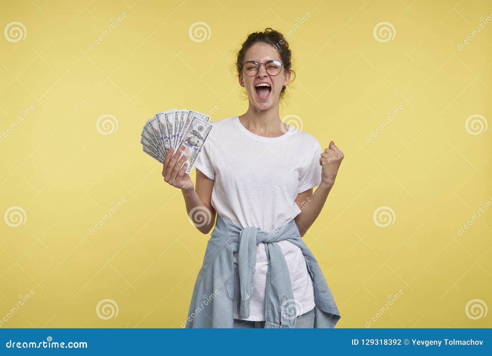 La giovane donna felice con capelli ricci tiene i lotti di contanti ed i grida della felicità,