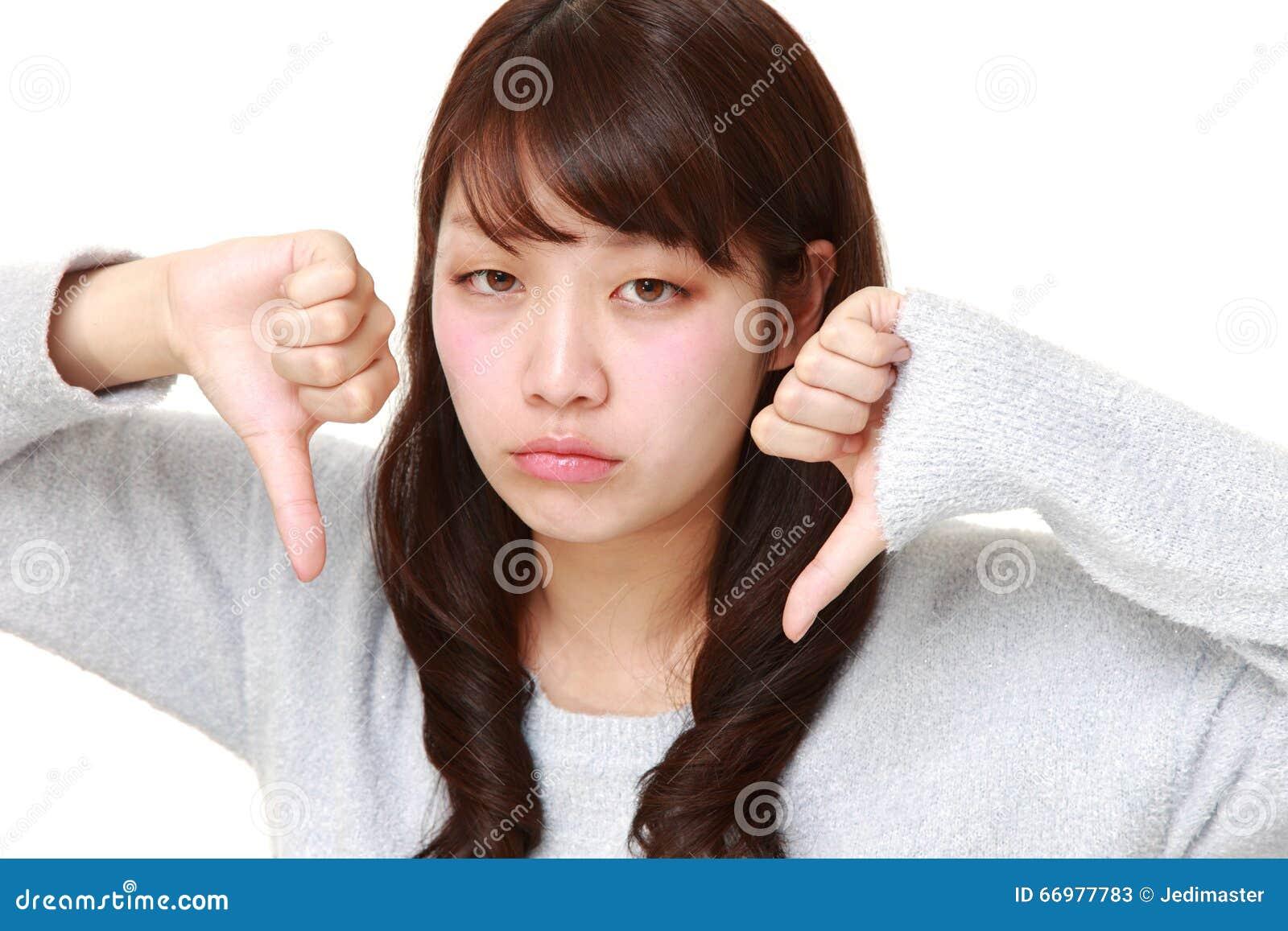 La giovane donna giapponese con i pollici giù gesture