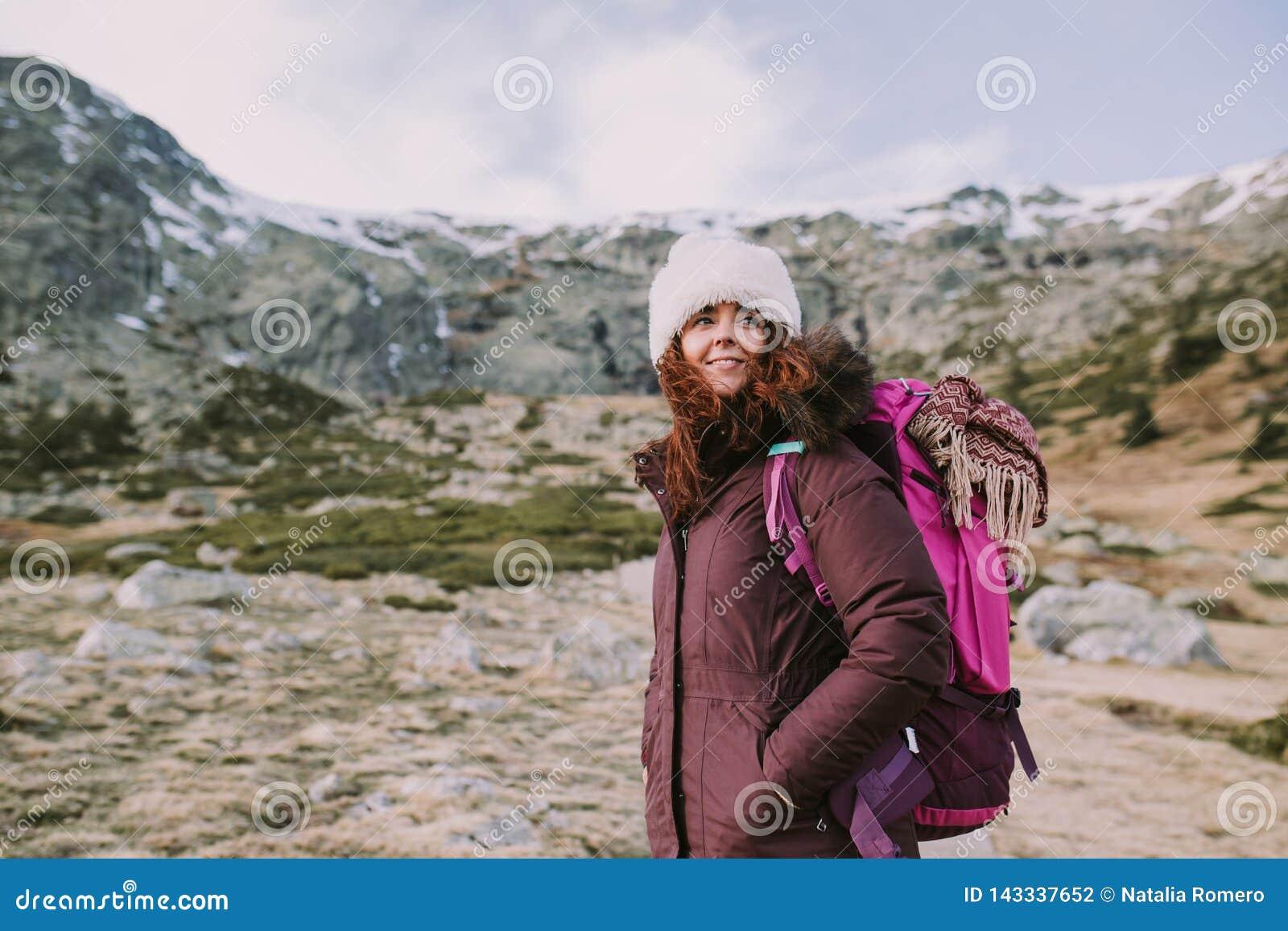 La giovane donna guarda lontano mentre gode della montagna